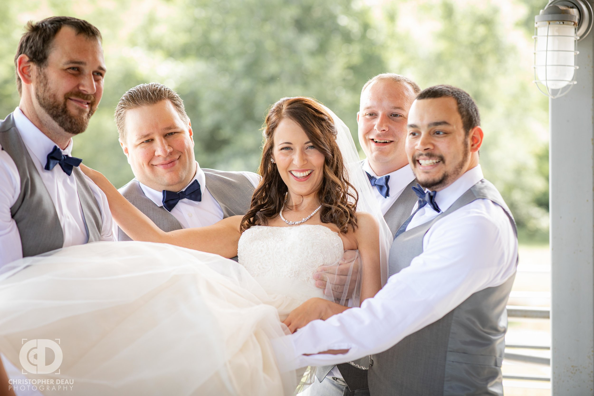 groomsmen lift up the bride