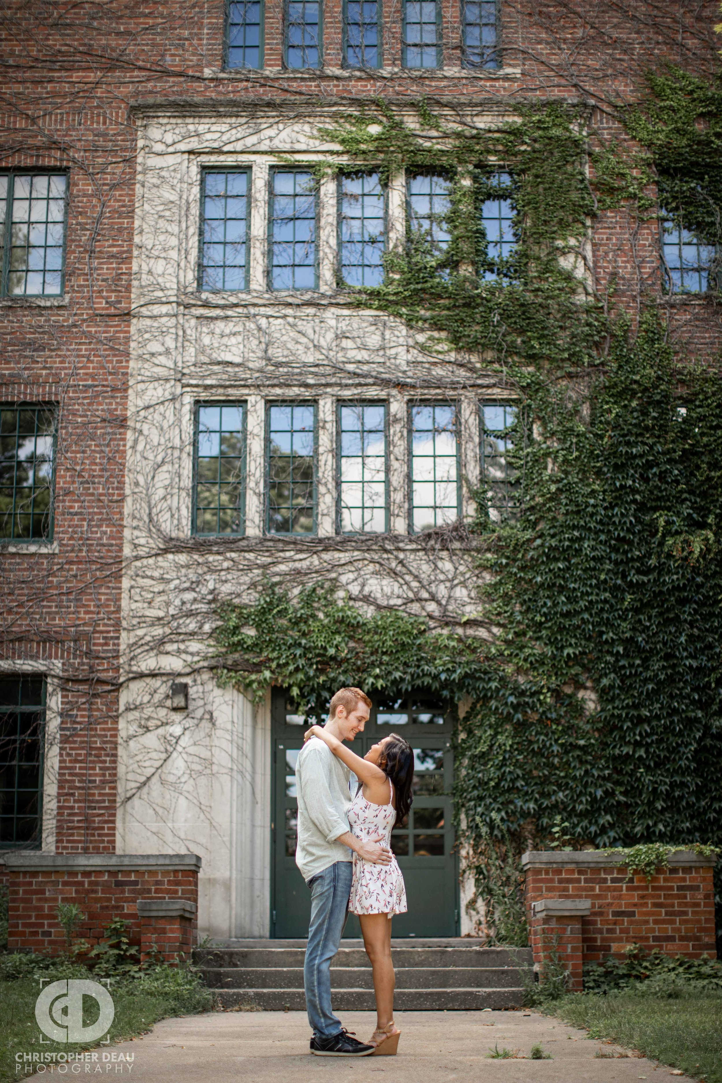 engaged couple in front of ivy covered building in Kalamazoo during photo session