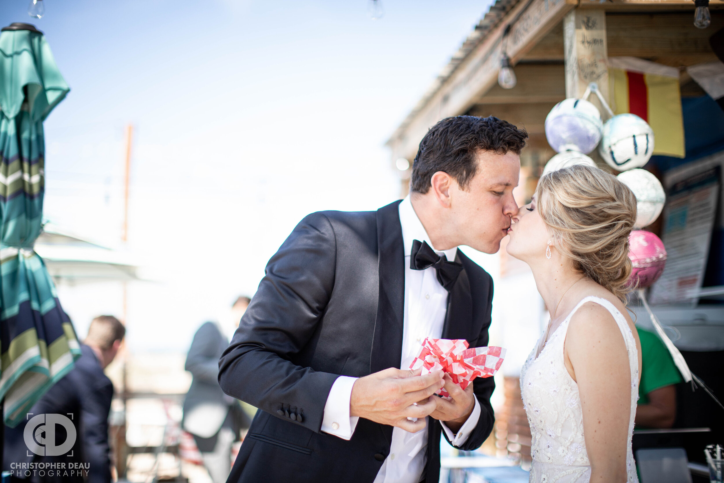 bride and groom find a hotdog stand at the beach and stop for a quick snack