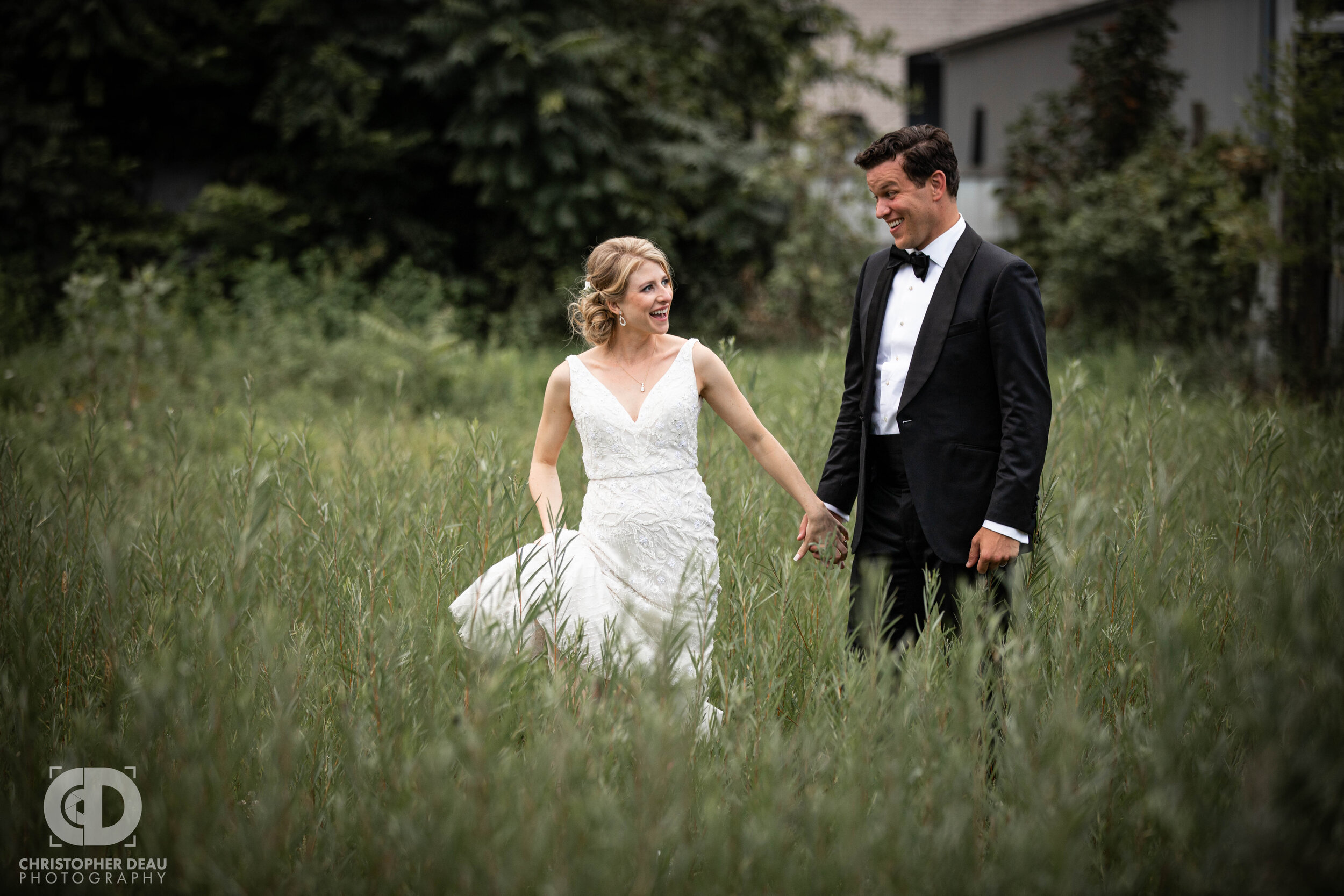 bride and groom in tall grass at journeyman distillery