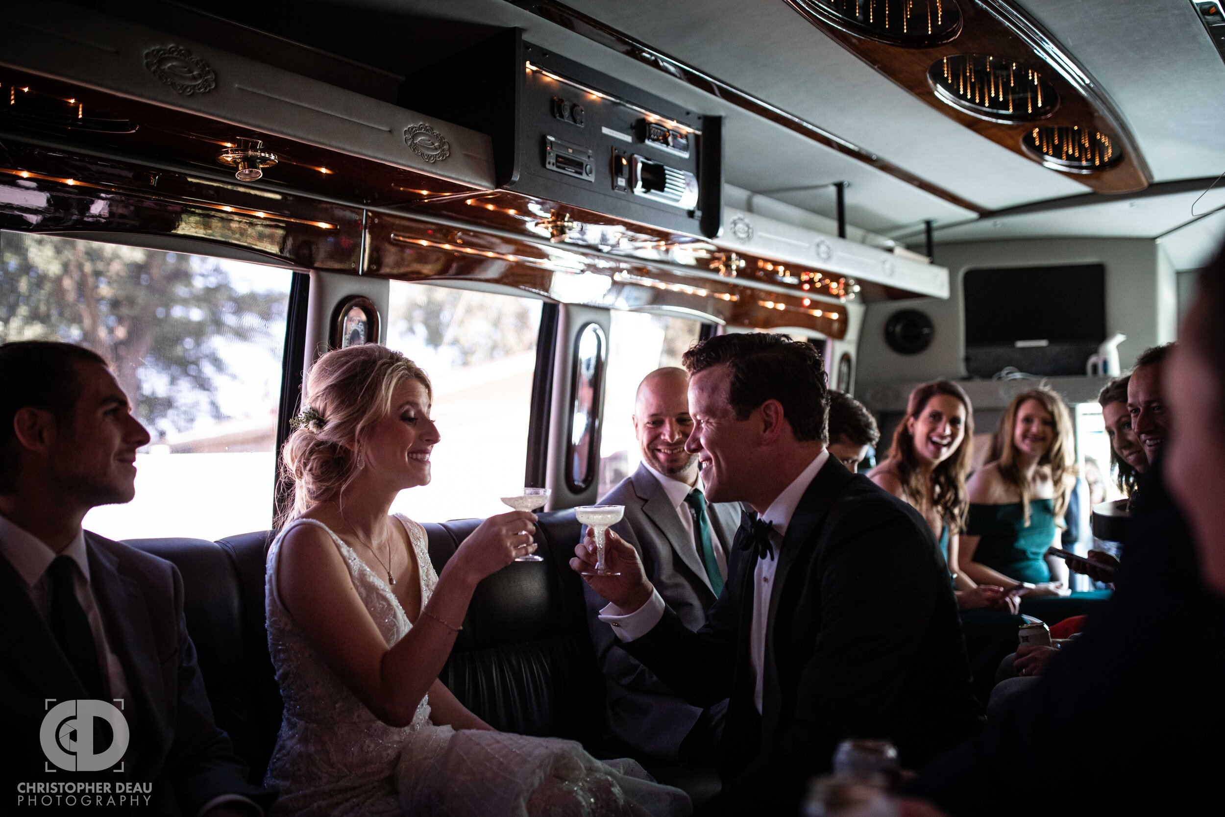bride and groom toast on the party bus