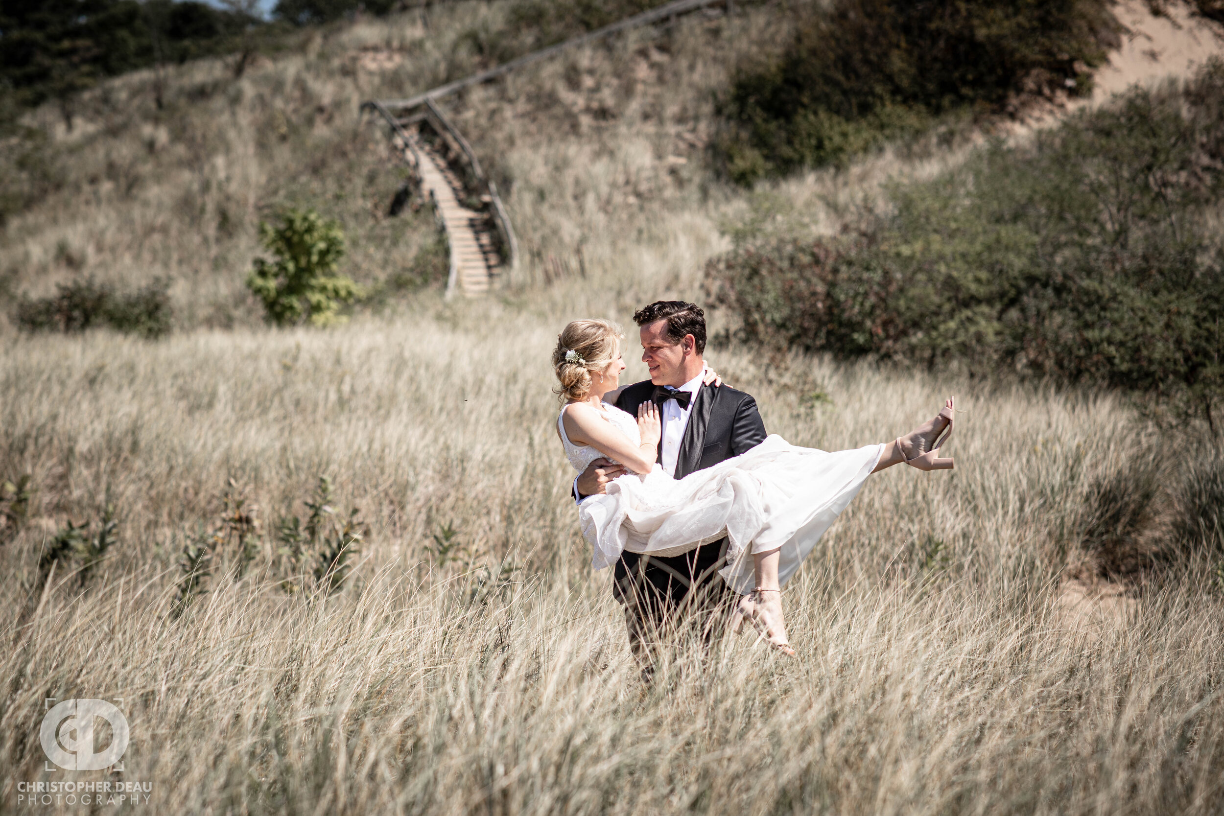 groom carries bride through tall beach grass along the shores of lake michigan