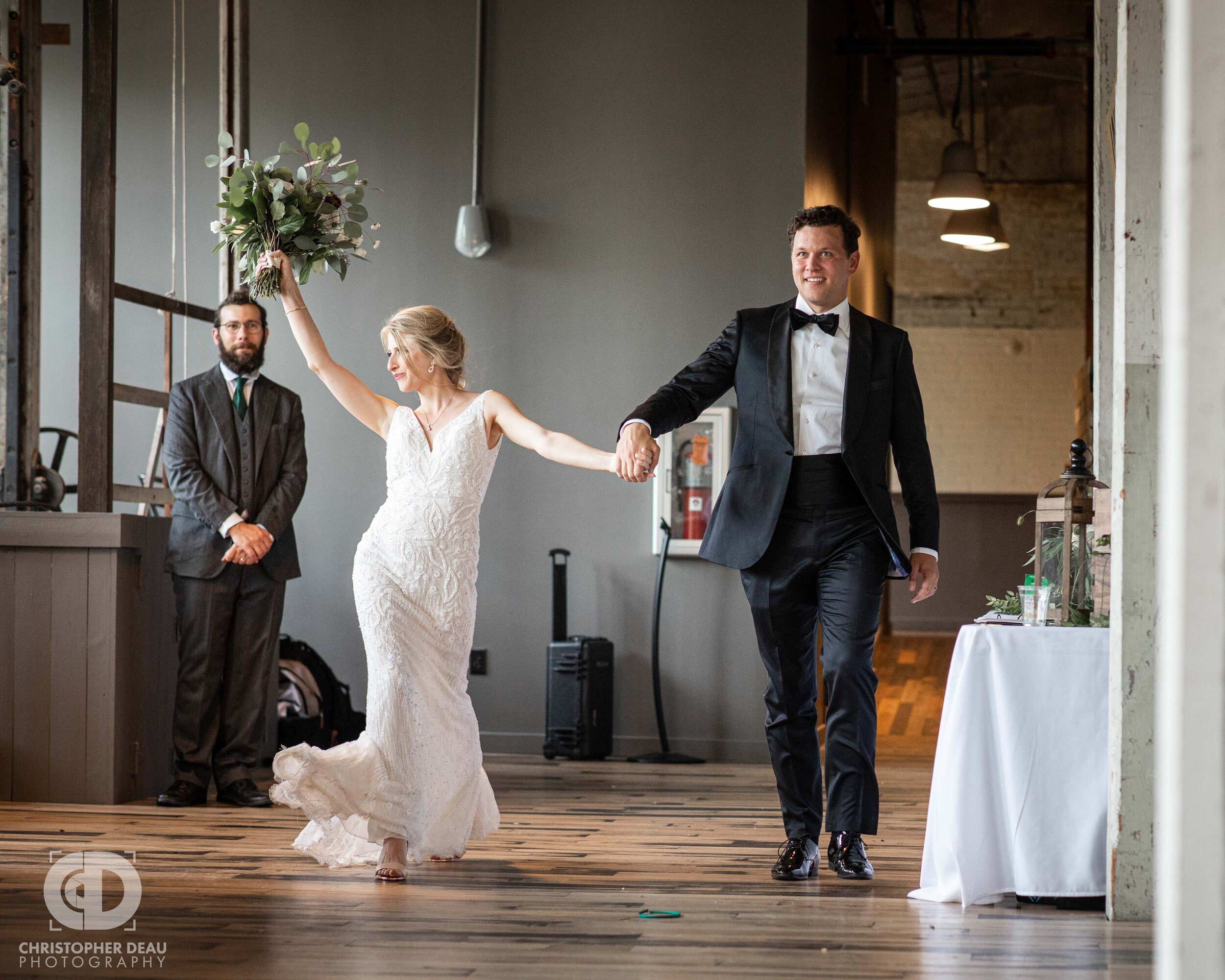bride and groom make a grand entrance at the journeyman distillery in saint joseph michigan