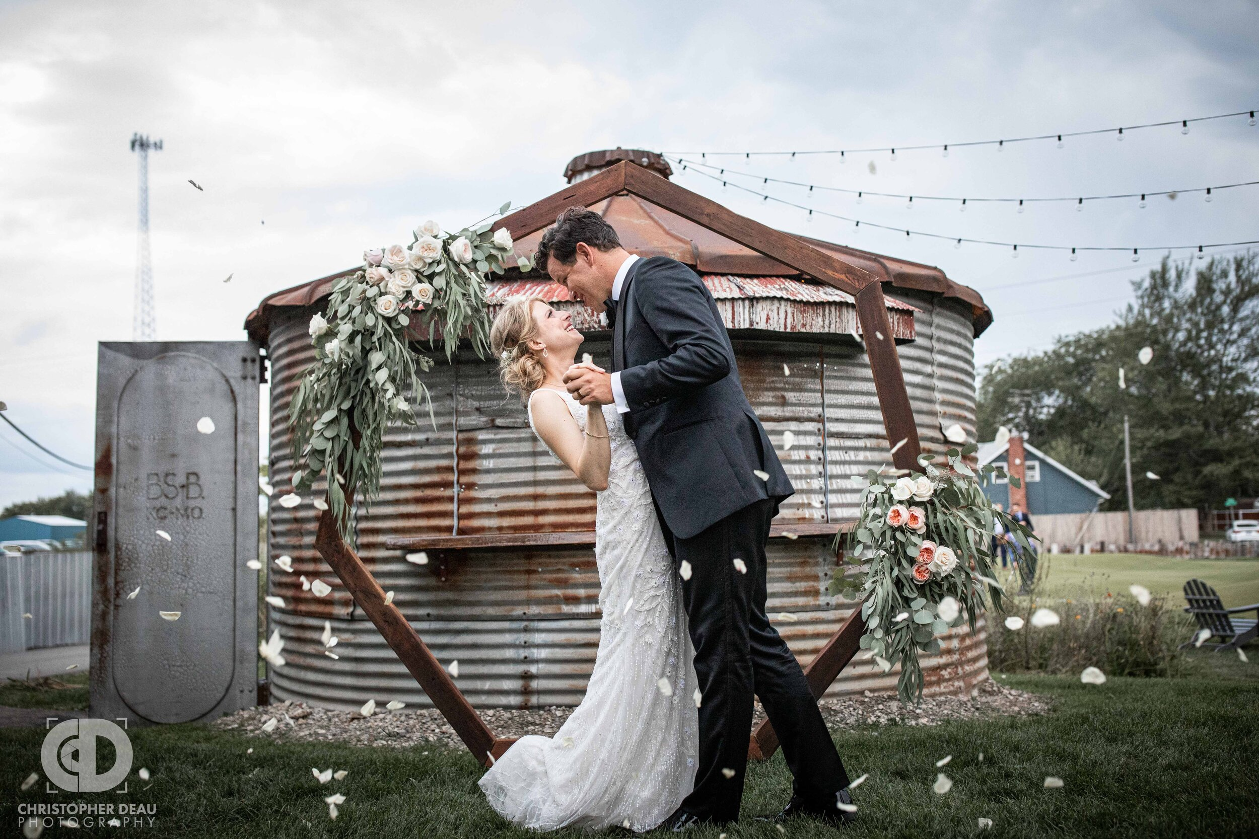 bride and groom first kiss with flower pedals tossed at journeyman distillery