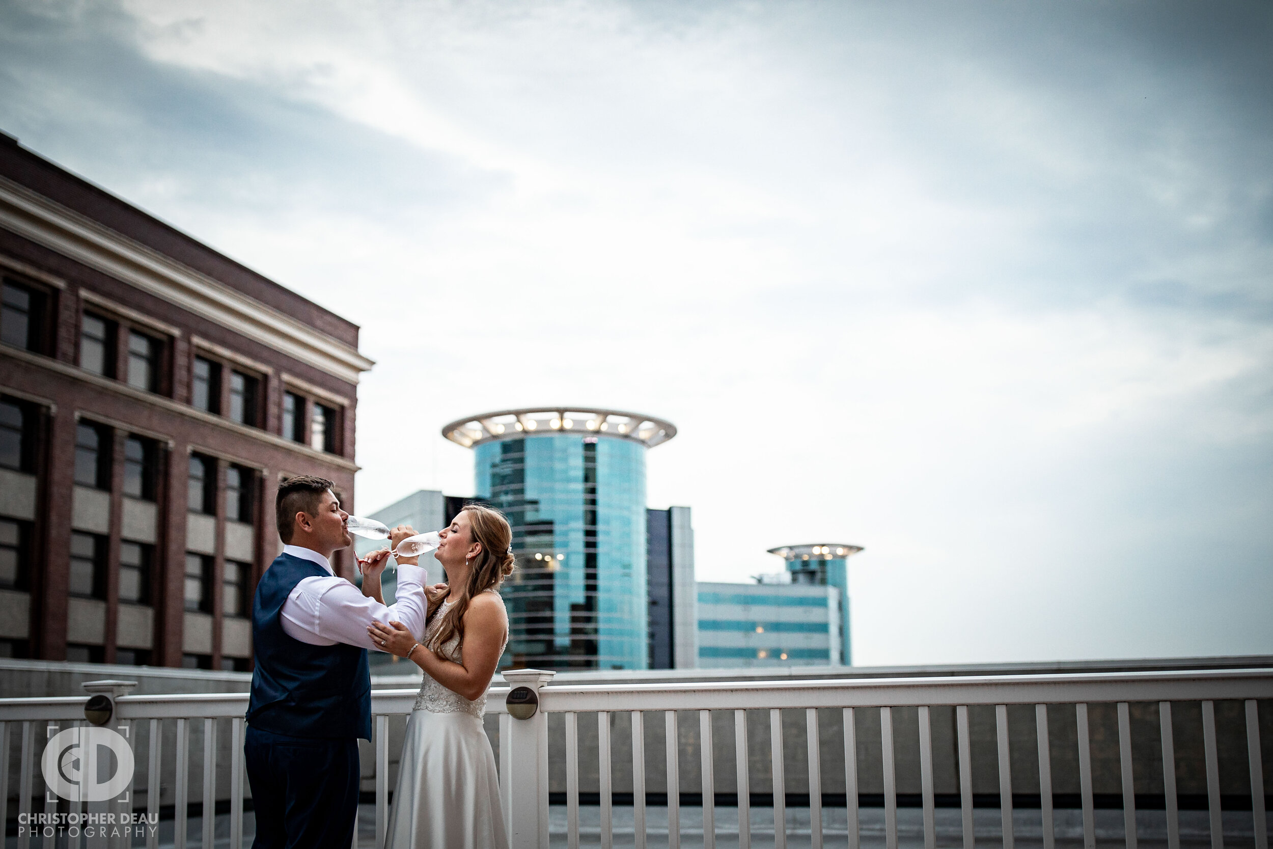 a rooftop toast with the bride and groom at cityscape in kalamazoo