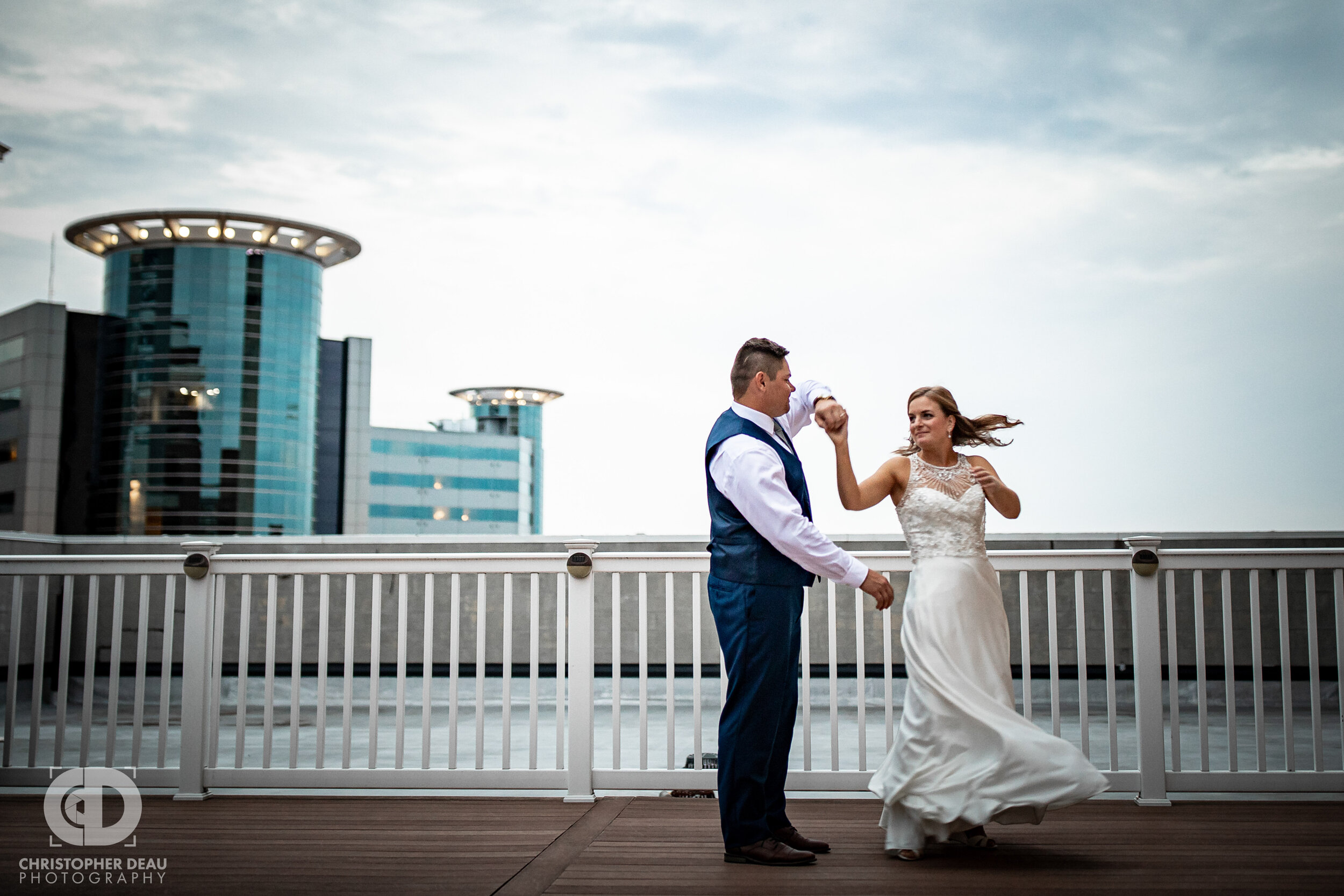 groom spins the bride on the rooftop of cityscape in Kalamazoo Michigan