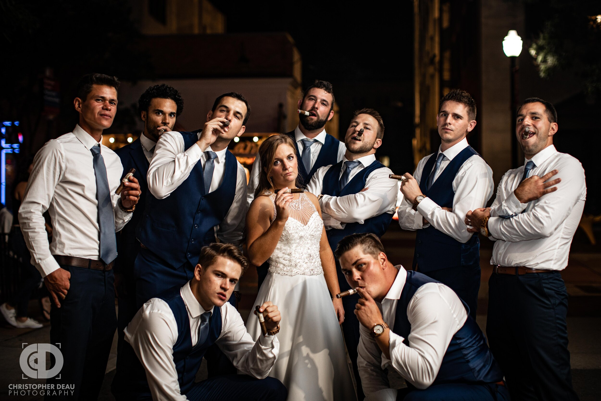 bride and groomsmen have cigars on the kalamazoo mall