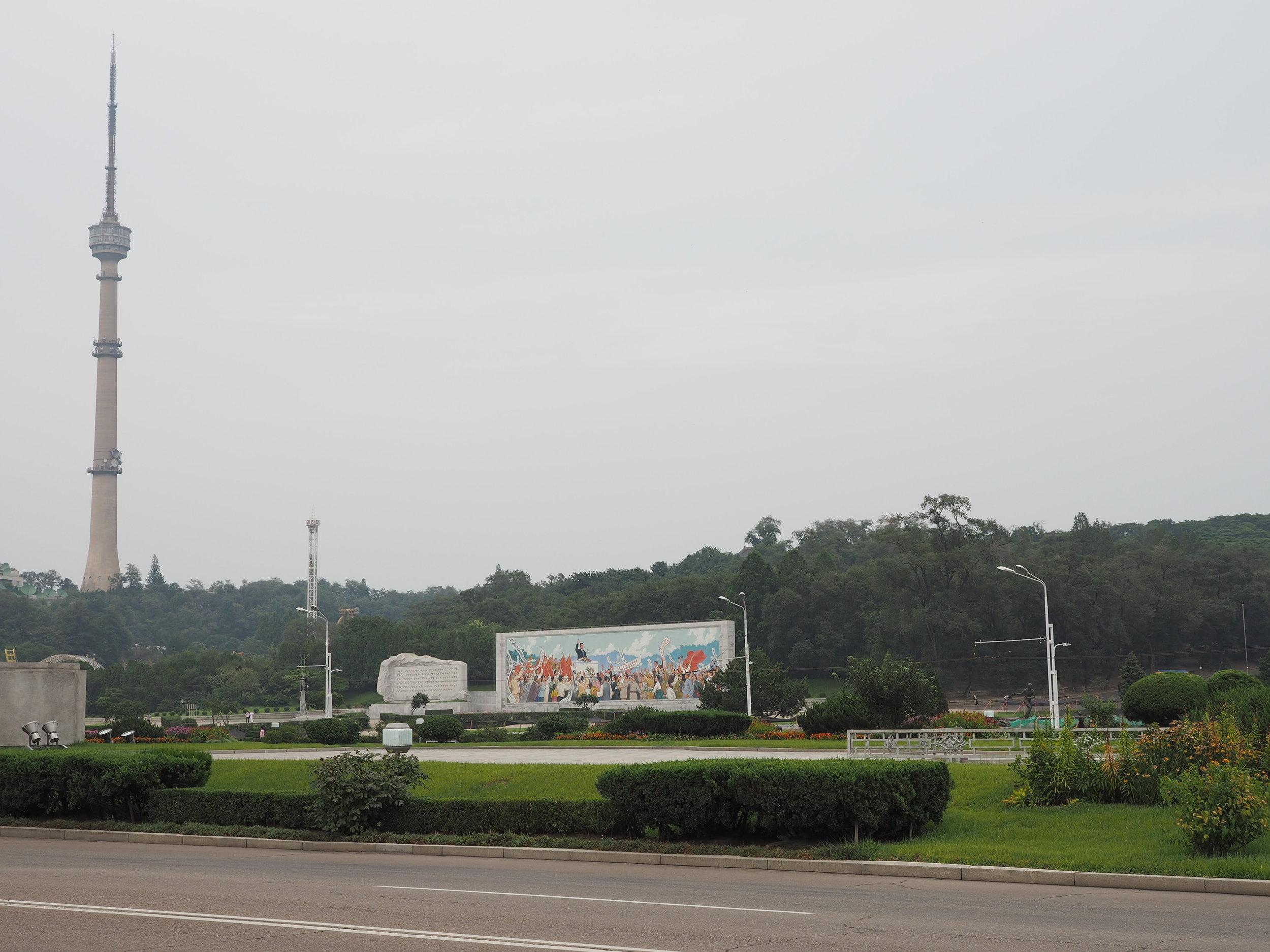 Pyongyang TV Tower next to a propaganda mural