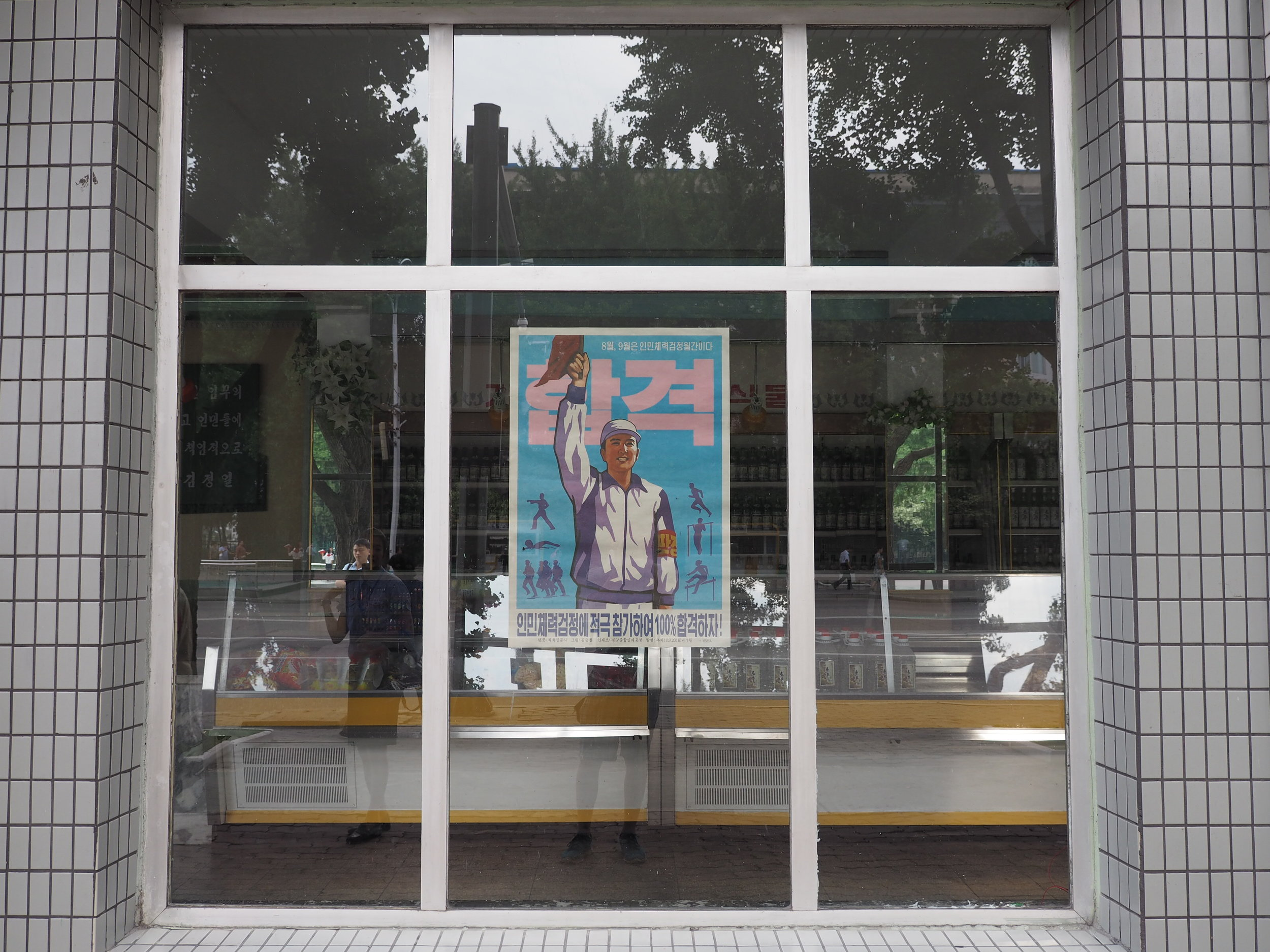 Propaganda poster on the window of a closed market
