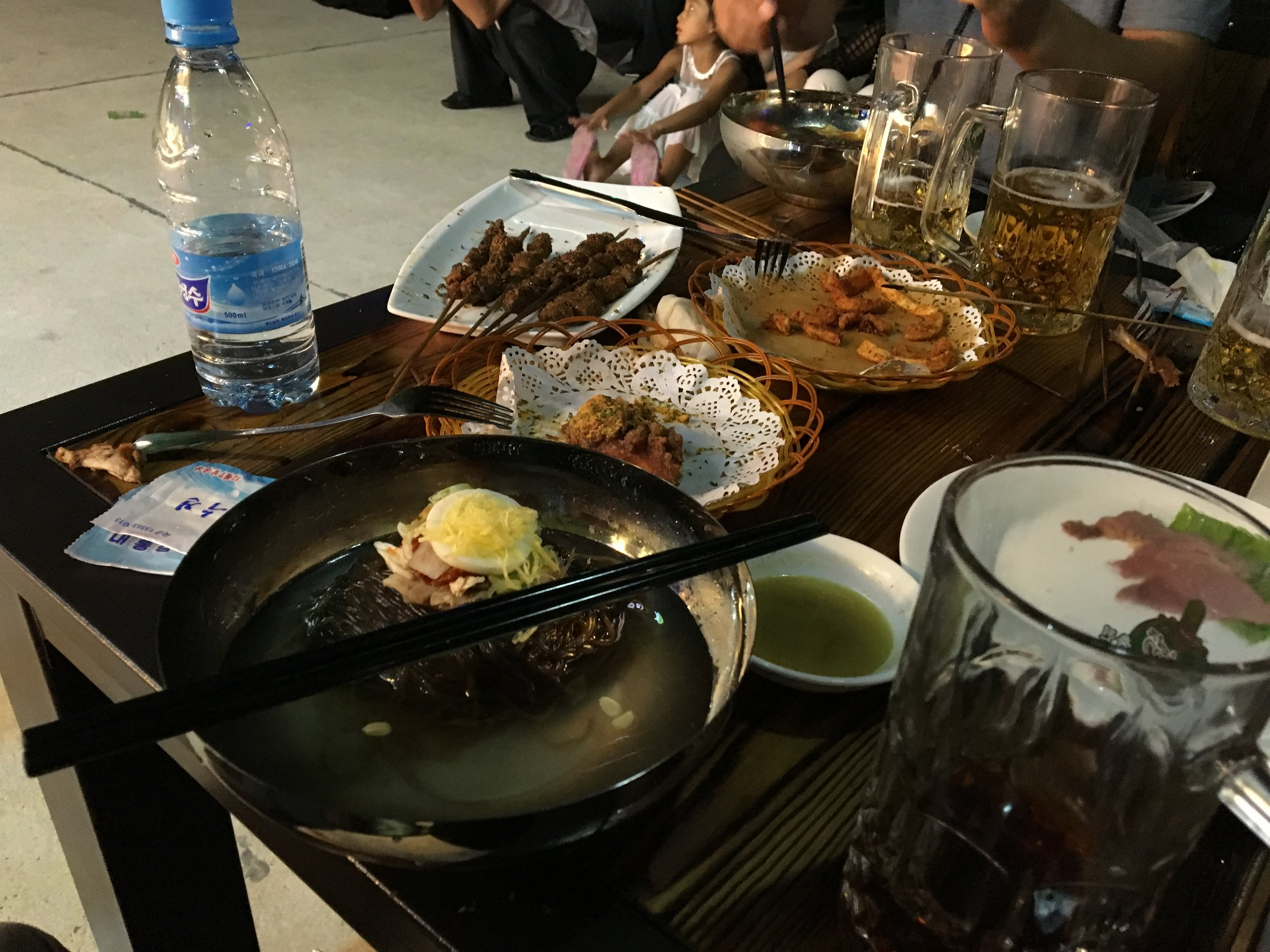 We shared a table with a North Korean family. They sand some lamb skewers, chicken wings, fries, and soba noodles.