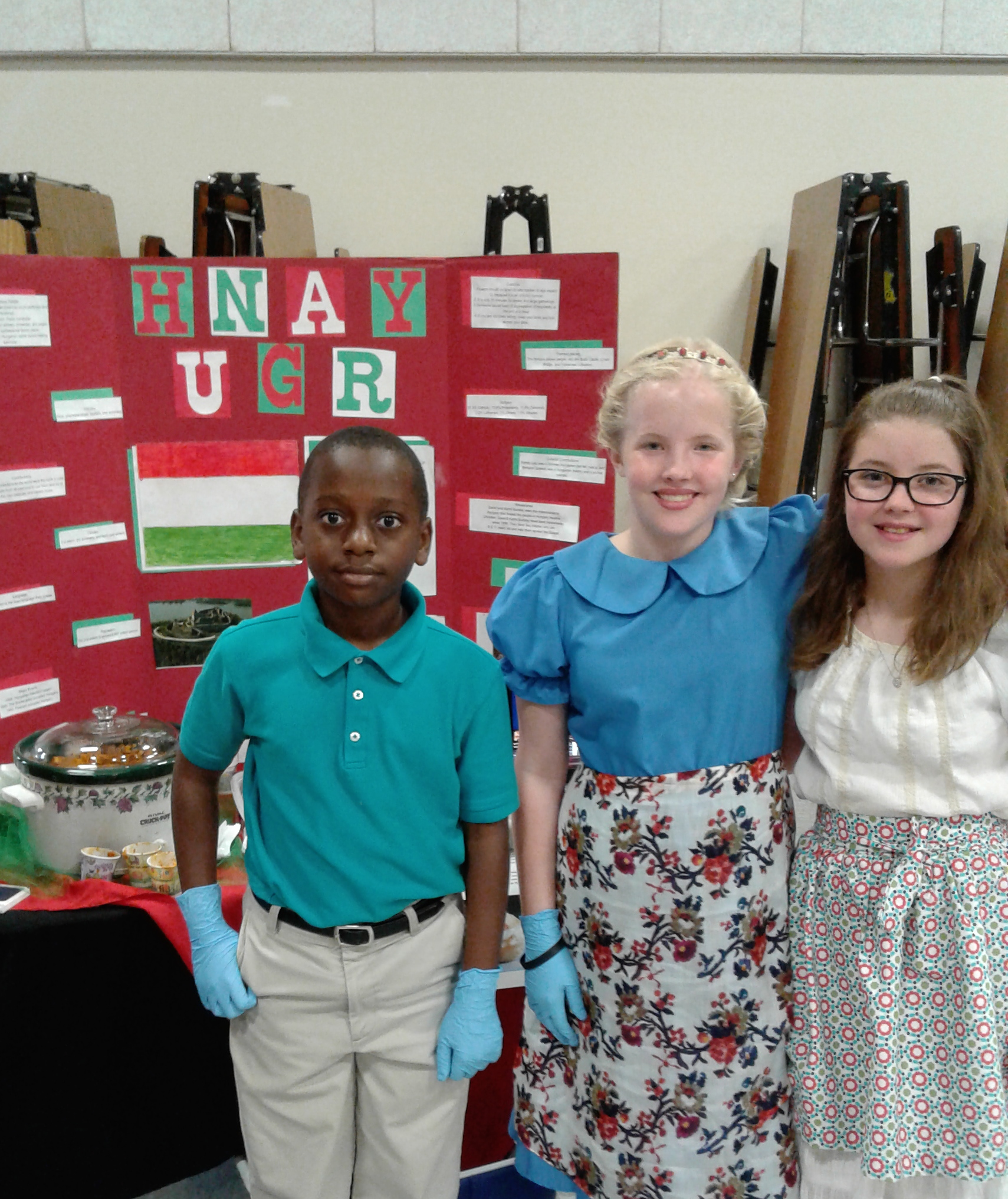 SCA fifth grade students, Samuel Mpinga, Caroline Hammett, and Emma Watson represented Hungary at the European Fair and provided Hungarian cinnamon bread, cream puffs, and goulash to their visitors.