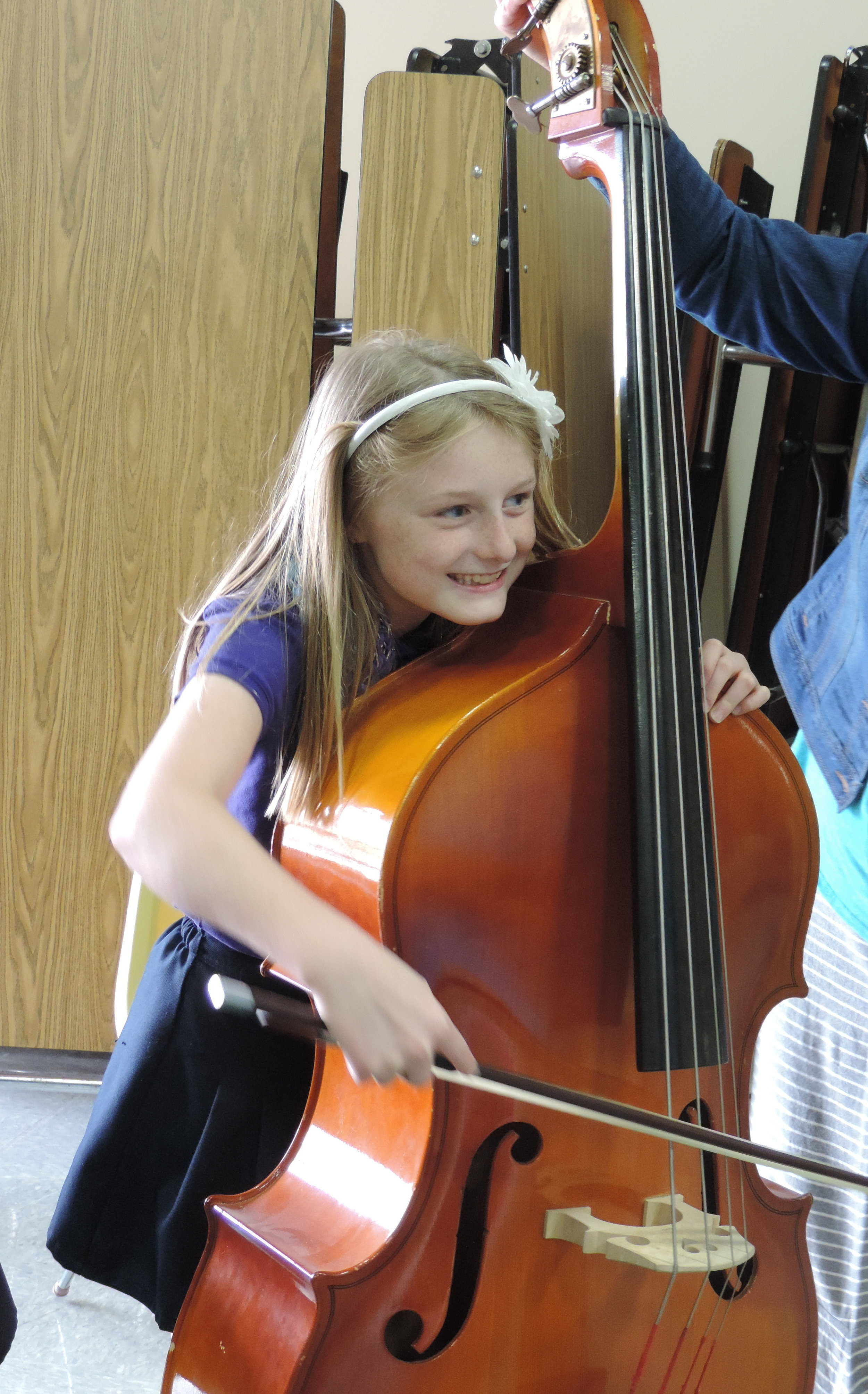 SCA fourth grade student Haley Sutton receives first-hand experience with the double bass thanks to the KC Symphony Petting Zoo.