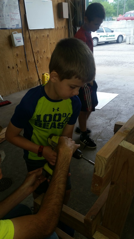 Maddox Hillmer (front) works on constructing the bench.