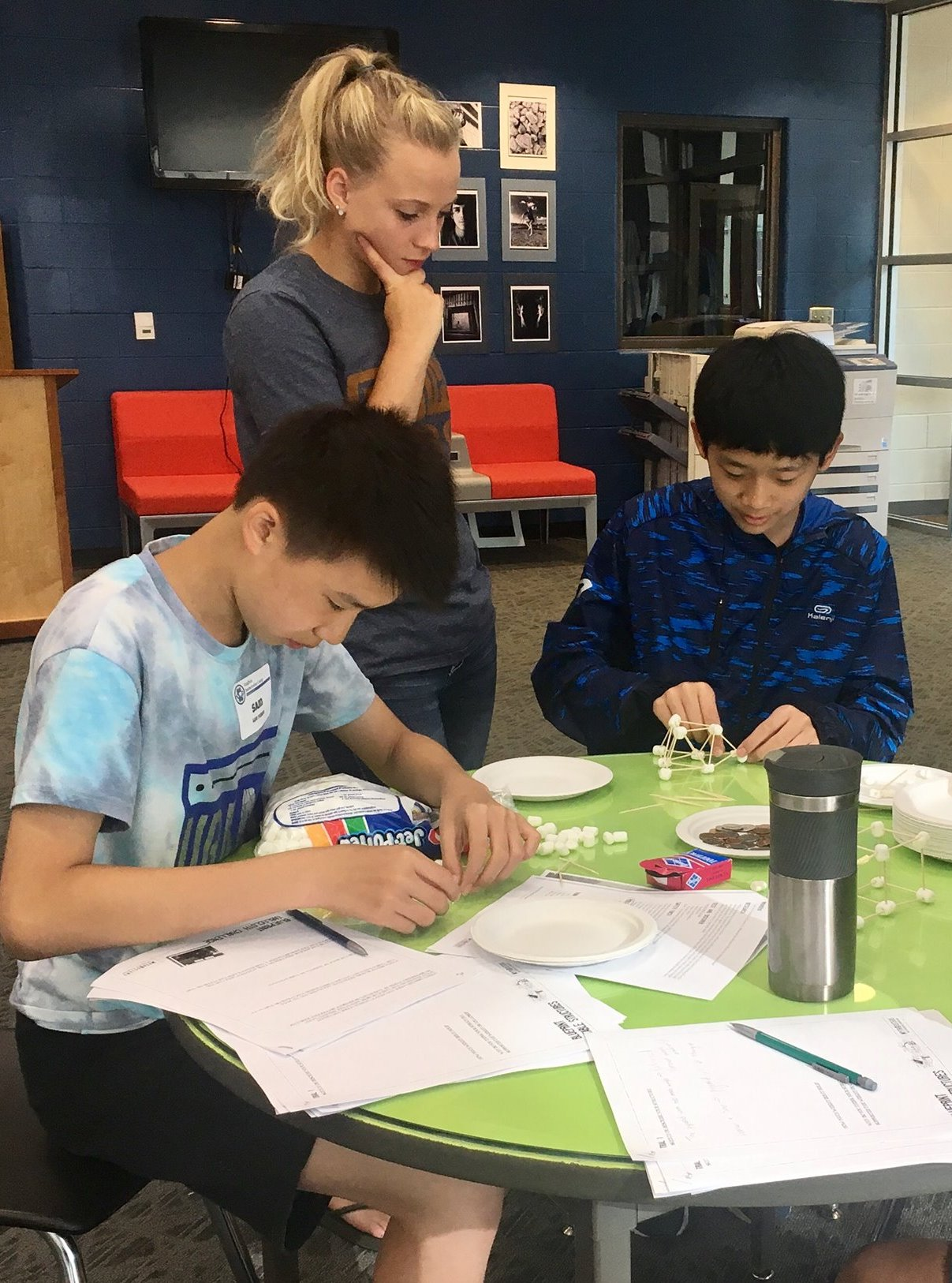 SCA Student Leader Abigail Woodall works with Chinese students during a warm-up activity, predicting the best shape for a structure that would hold the weight of a cup of pennies.