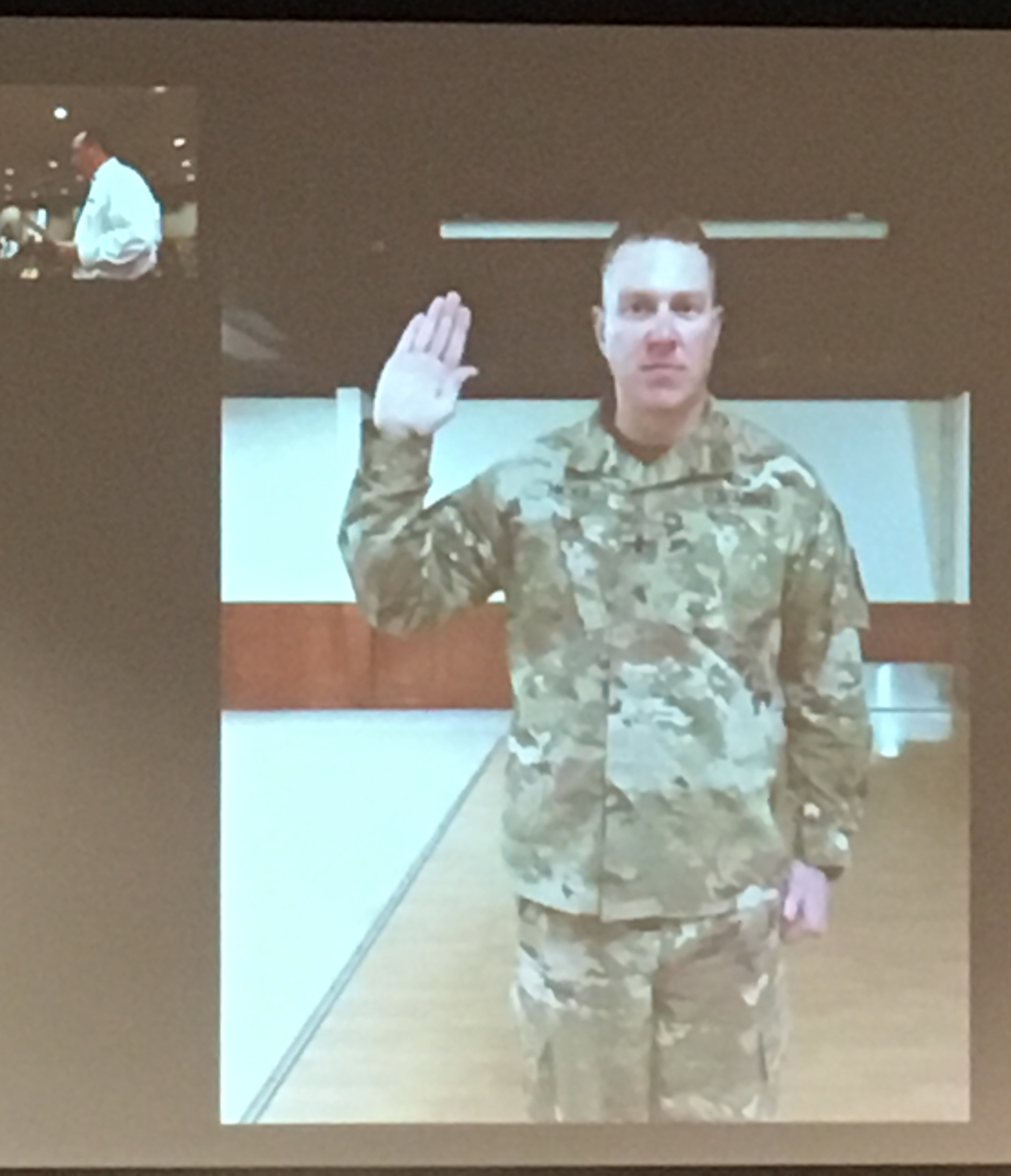 Captain Ben Hicks recites the oath for the position of captain via Facetime.
