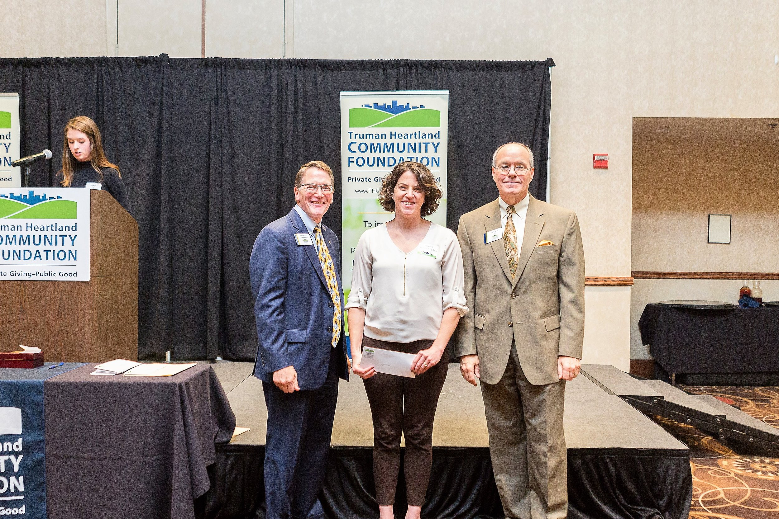 Rachel Segobia, center, accepts two grant checks from Truman Heartland Community Foundation President Phil Hanson and Chairman of the Board Cliff Jones.