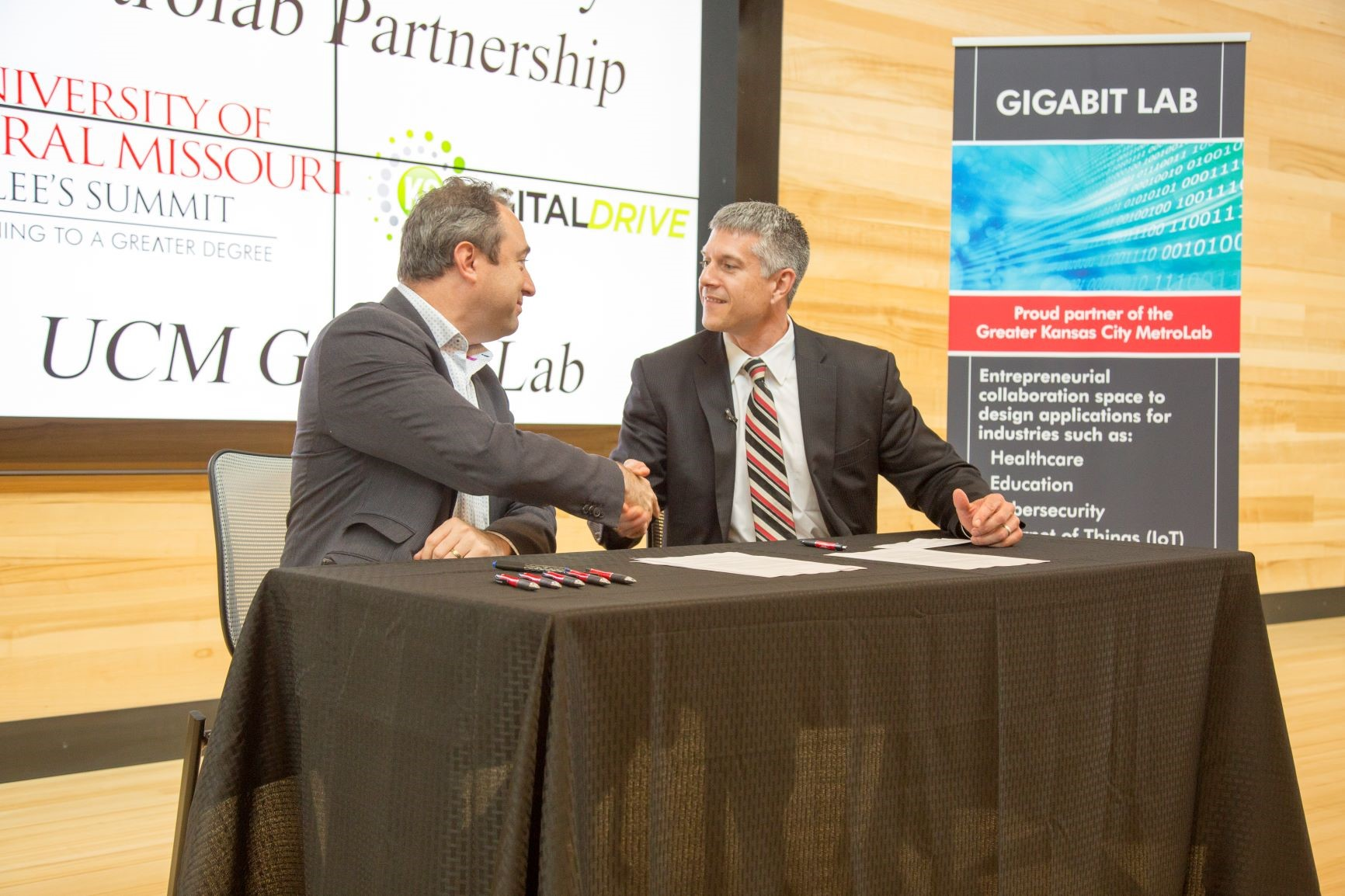 Aaron Deacon, left, managing director of KC Digital Drive, and Mike Godard, provost-chief learning officer for the University of Central Missouri, on Sept. 14 sign documents making possible UCM's participation in the Greater Kansas City MetroLab Partnership and the launching of a new Gigabit Lab at The Missouri Innovation Campus (MIC) in Lee's Summit.