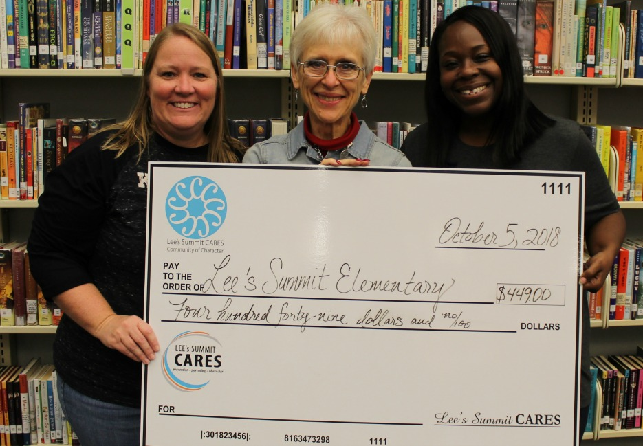 At an Oct. 5 grant presentation at Lee's Summit Elementary, Wendy Hilbert (left) and Daphne Mack (right), both staff members at the school, accept a check from Susan Coffman of Lee's Summit CARES. (Photo courtesy Lee's Summit CARES)
