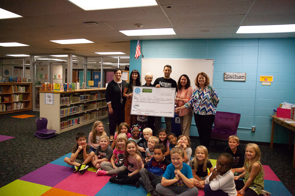 At an Oct. 10 grant presentation at Prairie View Elementary, staff members and 1st grade students accept a check from Susan Coffman of Lee's Summit CARES (middle left) and TJ Rejak of Xtreme Gymnastics. (Photo courtesy Lee's Summit CARES)