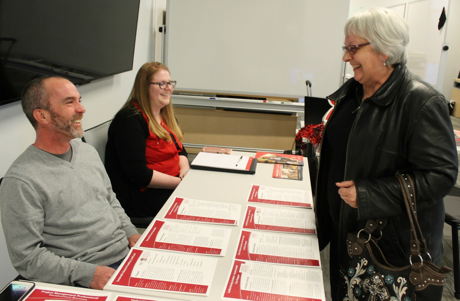 Scott Boyce and Katie Honomichl of the University of Central Missouri talk to Theresa Leaming during the Feb. 26 event.   (Photo courtesy UCM-Lee's Summit)