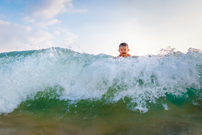 This image of my daughter is actually only a few feet form the shoreline, in waist deep water (my husband is holding her and hiding behind the wave). You don't necessarily have to go far out to get fun shots!