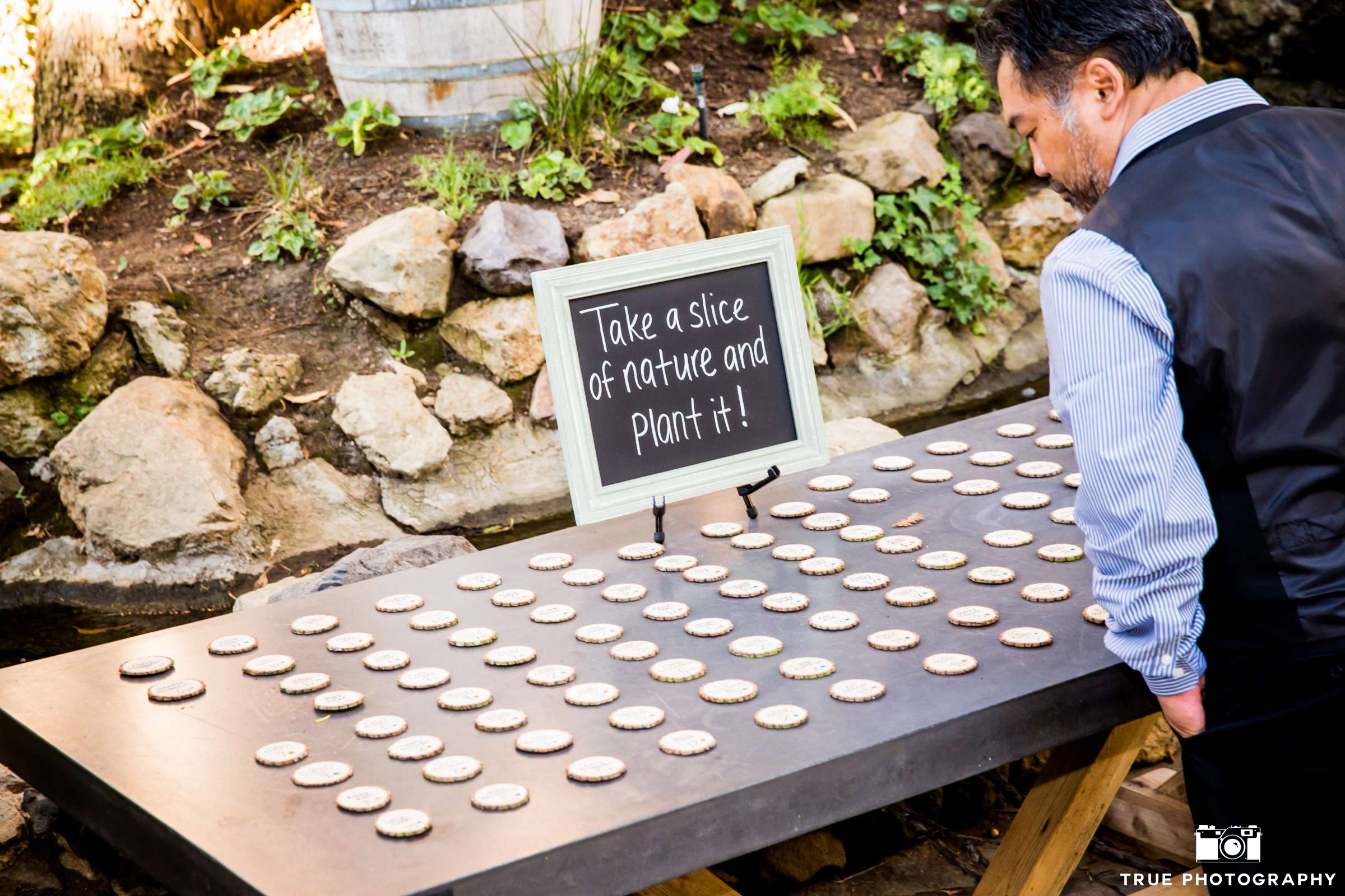 I love seeing reflections of couples' personalities!  The signage is reminiscent of the bride and groom's sense of humor, and escort cards made of wood slices and calligraphy by friends of the bride and groom guide guests to their seats. Photo by  True Photography.