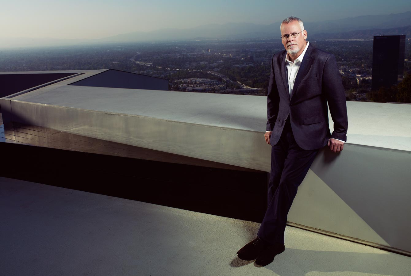 Mark DeLong - Celebrity Photographer - Male Celebrity wearing a suit stands on top of a roof.