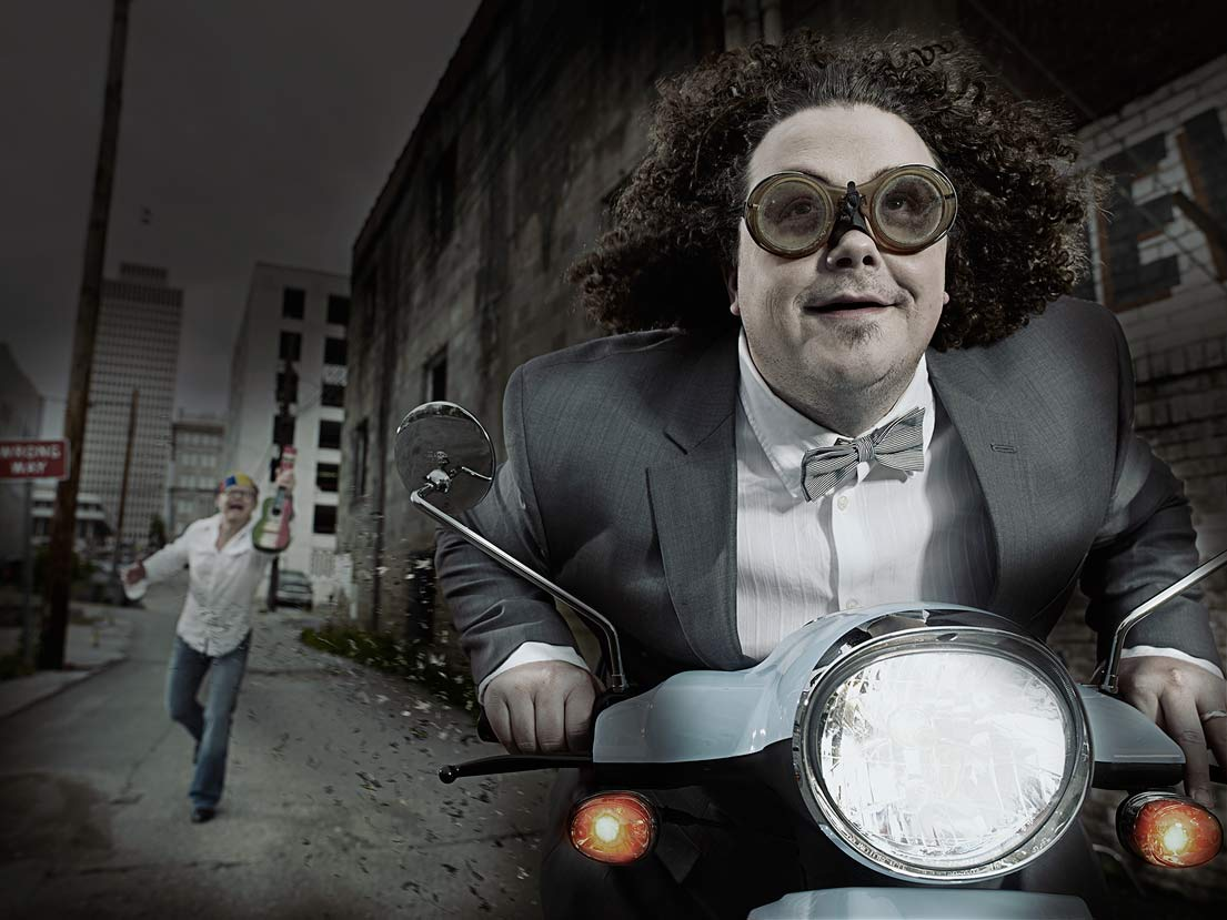 Mark DeLong - Celebrity Photographer - Actor riding a moped wearing thick goggles.