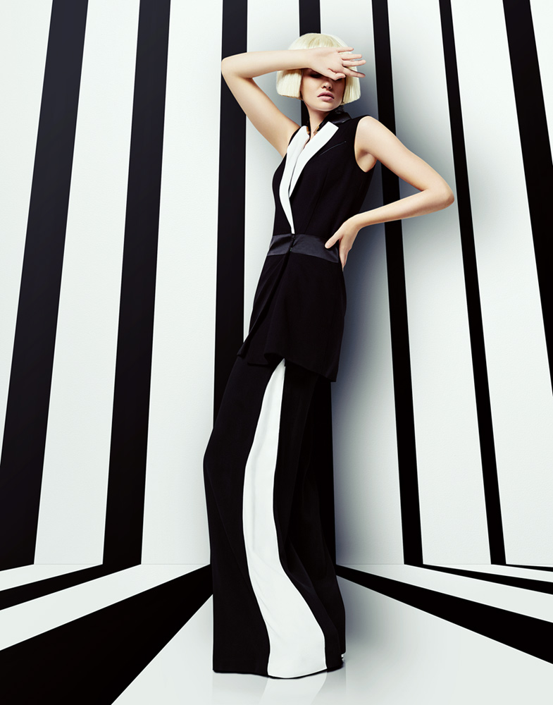 Blond woman with short hair wearing black and white outfit in front of black and white striped background - Mark DeLong: Fashion Gallery