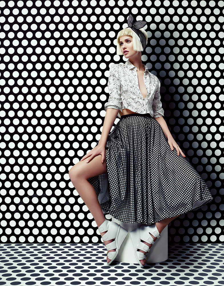 Woman with short blond hair wearing luxury printed top and dress sitting in a honeycomb black and white background - Mark DeLong: Fashion Gallery