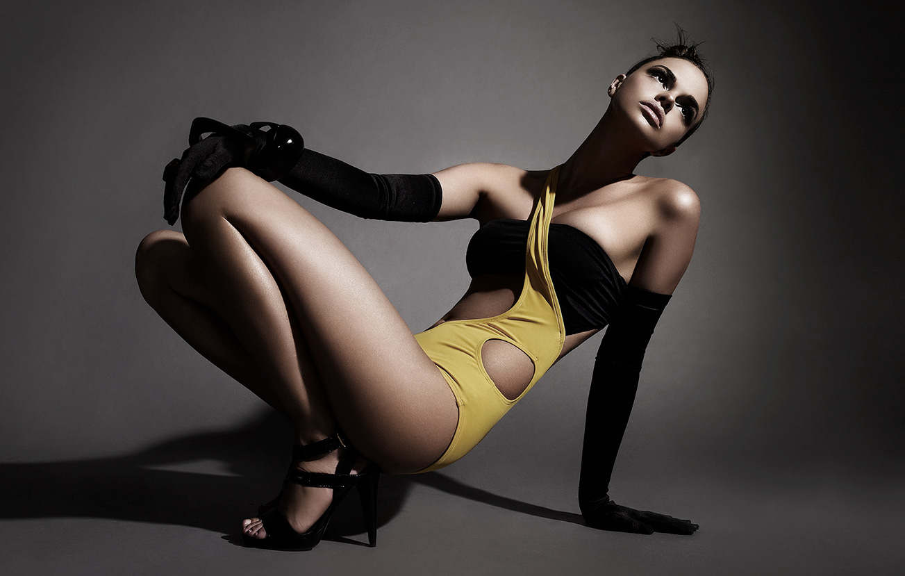 Tan woman crouching in yellow and black abstract outfit with long black gloves - Mark DeLong: Fashion Gallery