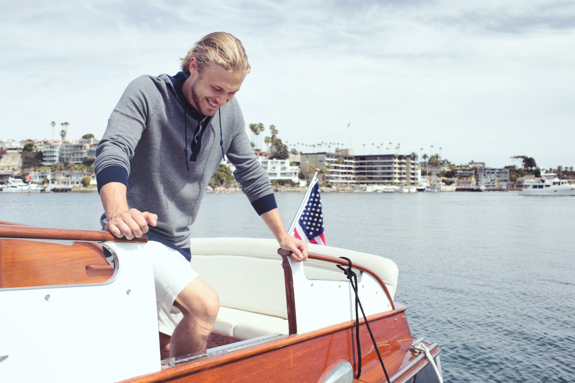Mark DeLong - Lifestyle Photography - Man in a blue sweatshirt stepping off of a cris craft boat