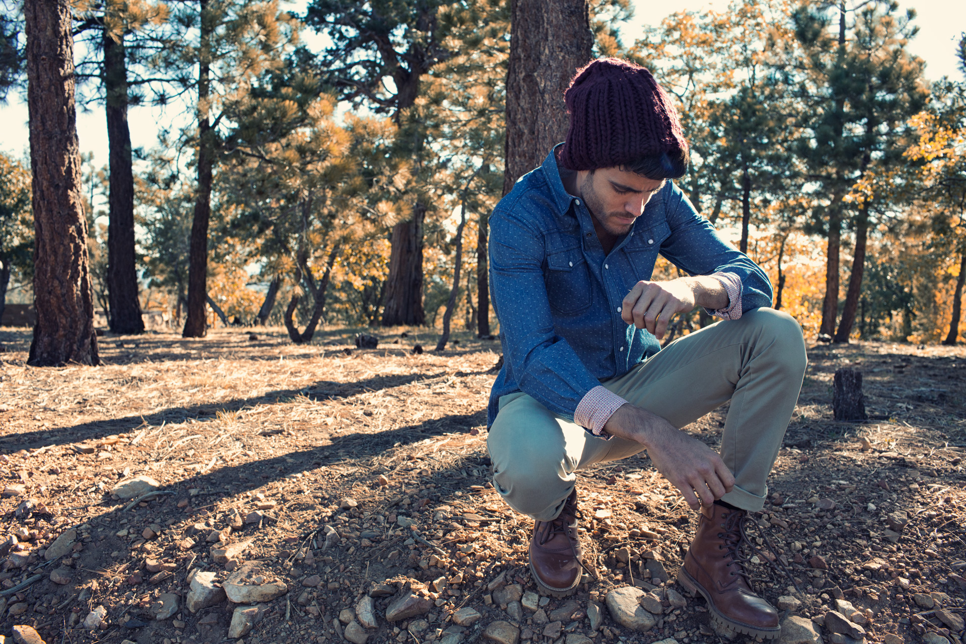 Mark DeLong - Lifestyle Photography - Model wearing a dark red beanie bending down to fix his shoe
