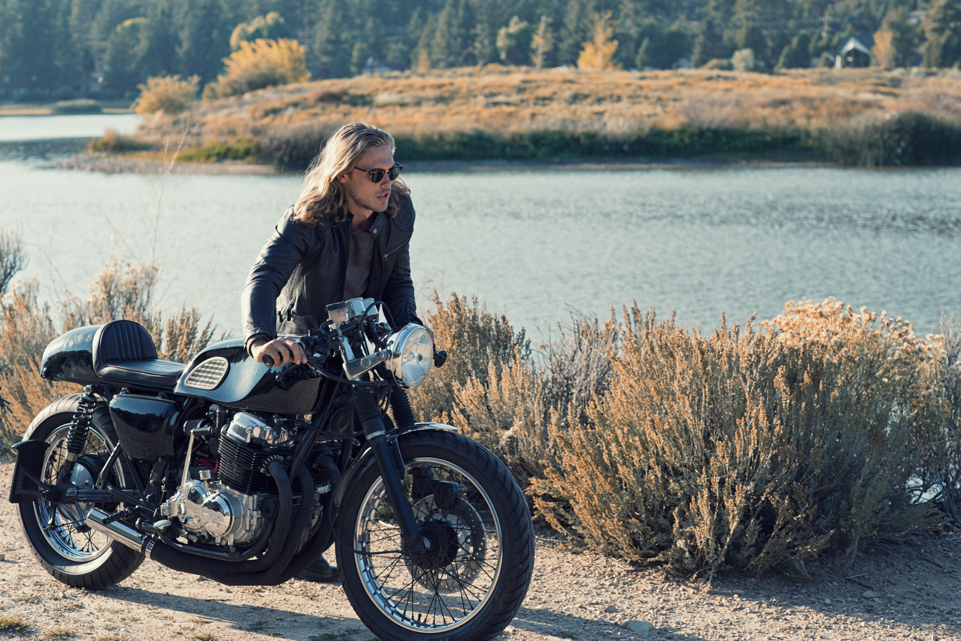 Mark DeLong - Lifestyle Photography - Model with long blonde hair wearing sunglasses pushing a motorcycle along the bank of a lake