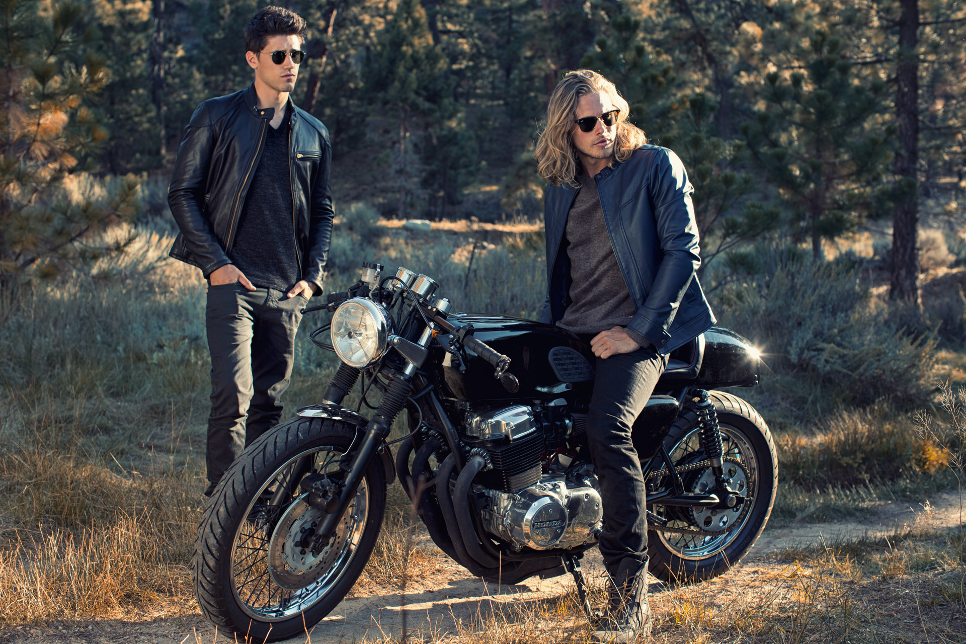 Mark DeLong - Lifestyle Photography - Man sitting on motorcycle wearing sunglasses and a man standing by the motorcycle wearing a leather jacket