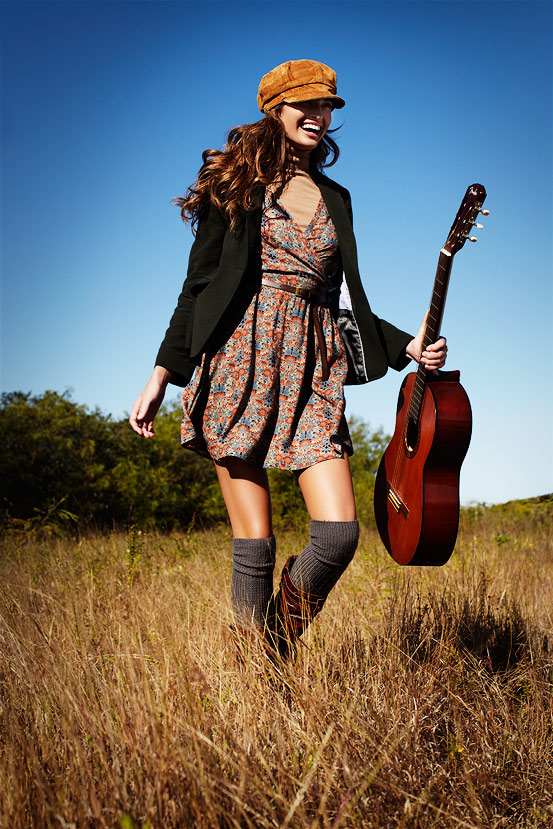 Mark DeLong - Lifestyle Photography - A brunette girl in a yellow hat in knee high socks walking through a field holding a guitar