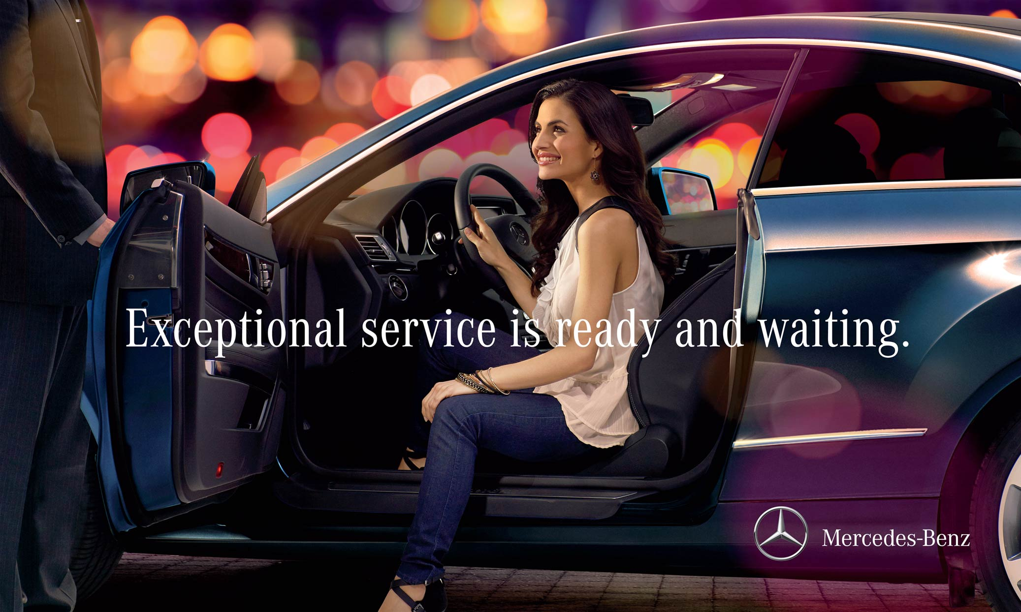 Mark DeLong - Commercial Photography - Man holding door for a woman getting out of a Mecedes-Benz.