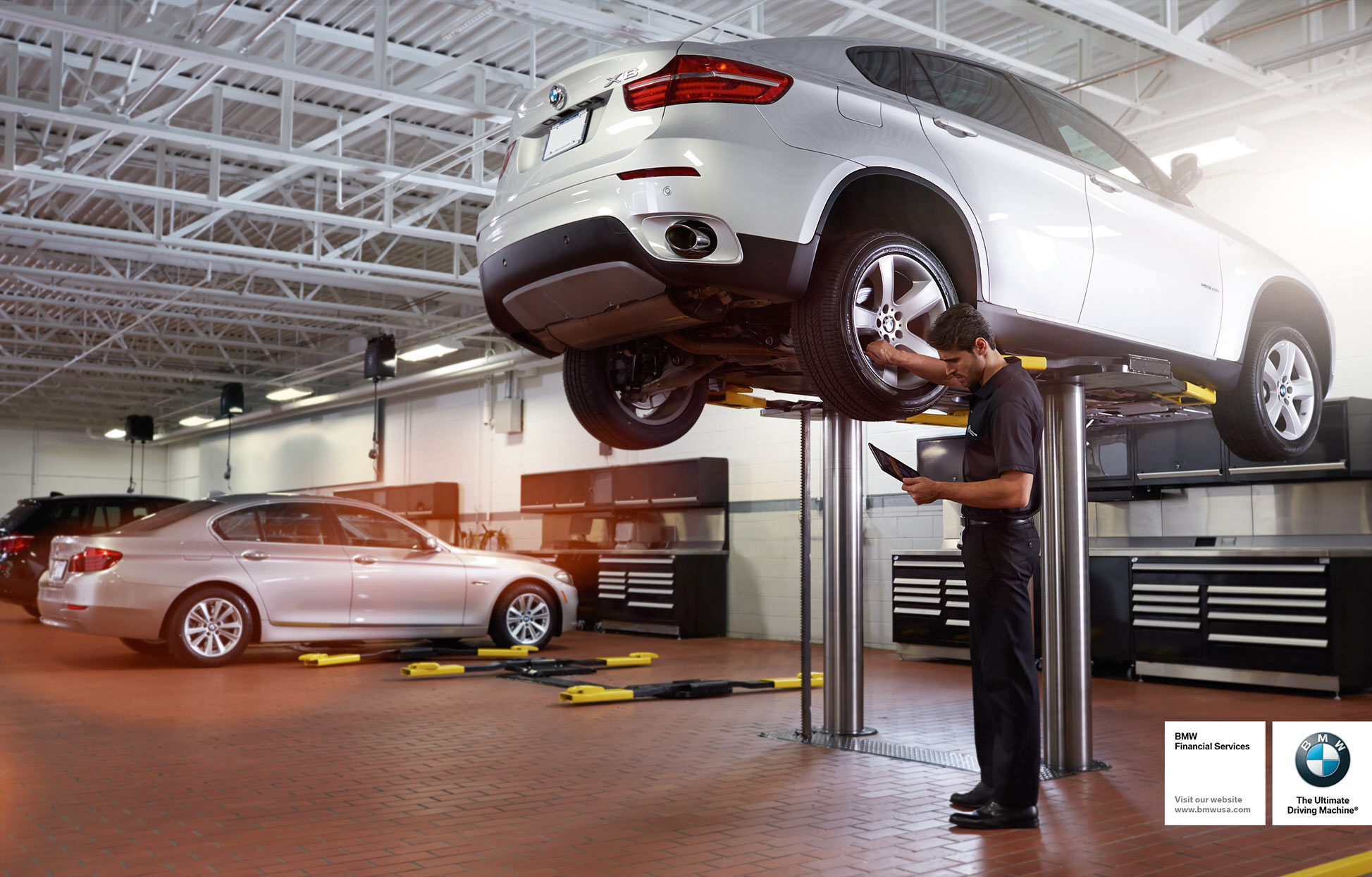 Mark DeLong - Commercial Photography - Man in a car garage inspecting the wheel base of a BMW that is raised up in a lift.