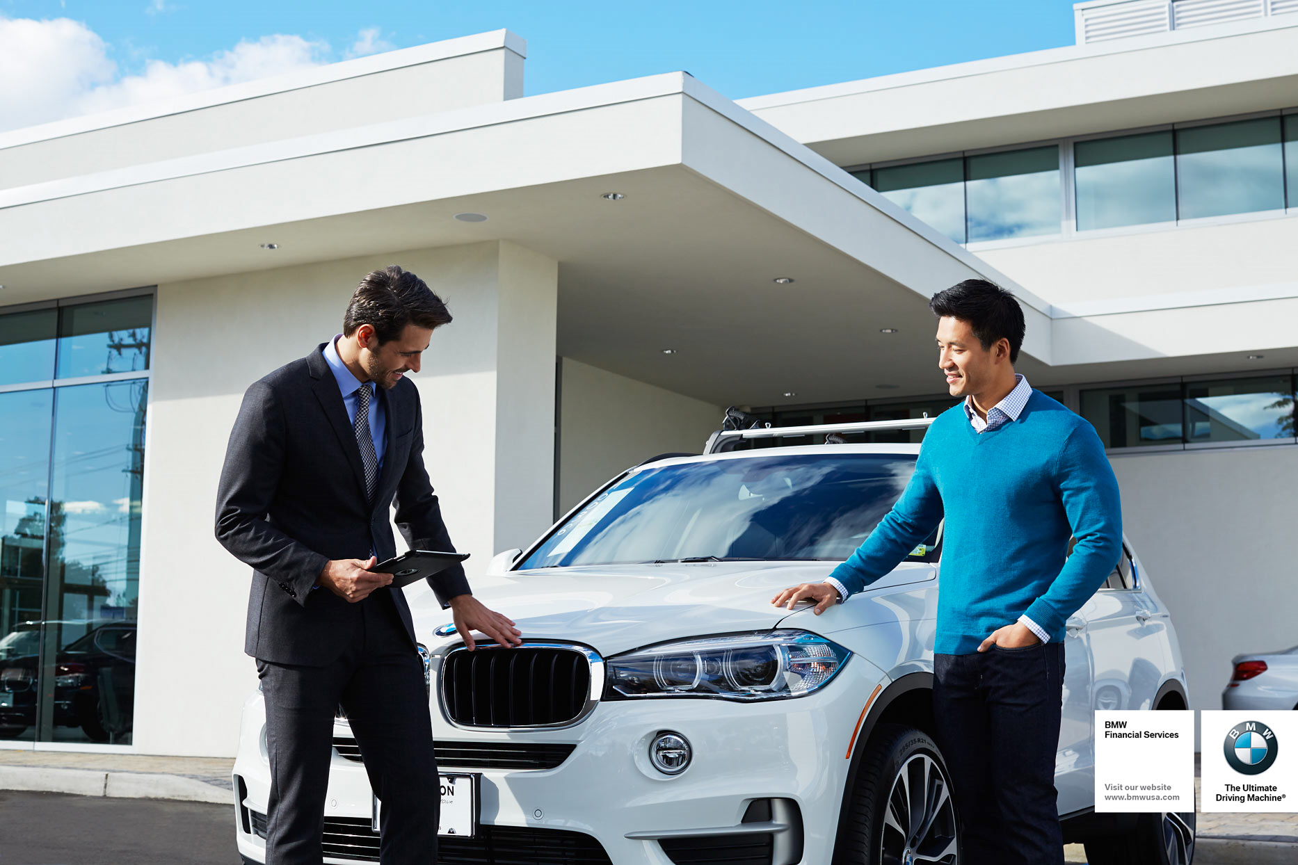 Mark DeLong - Commercial Photography - Man in blue sweater talking to a car salesman in a suit in front of a white SUV.