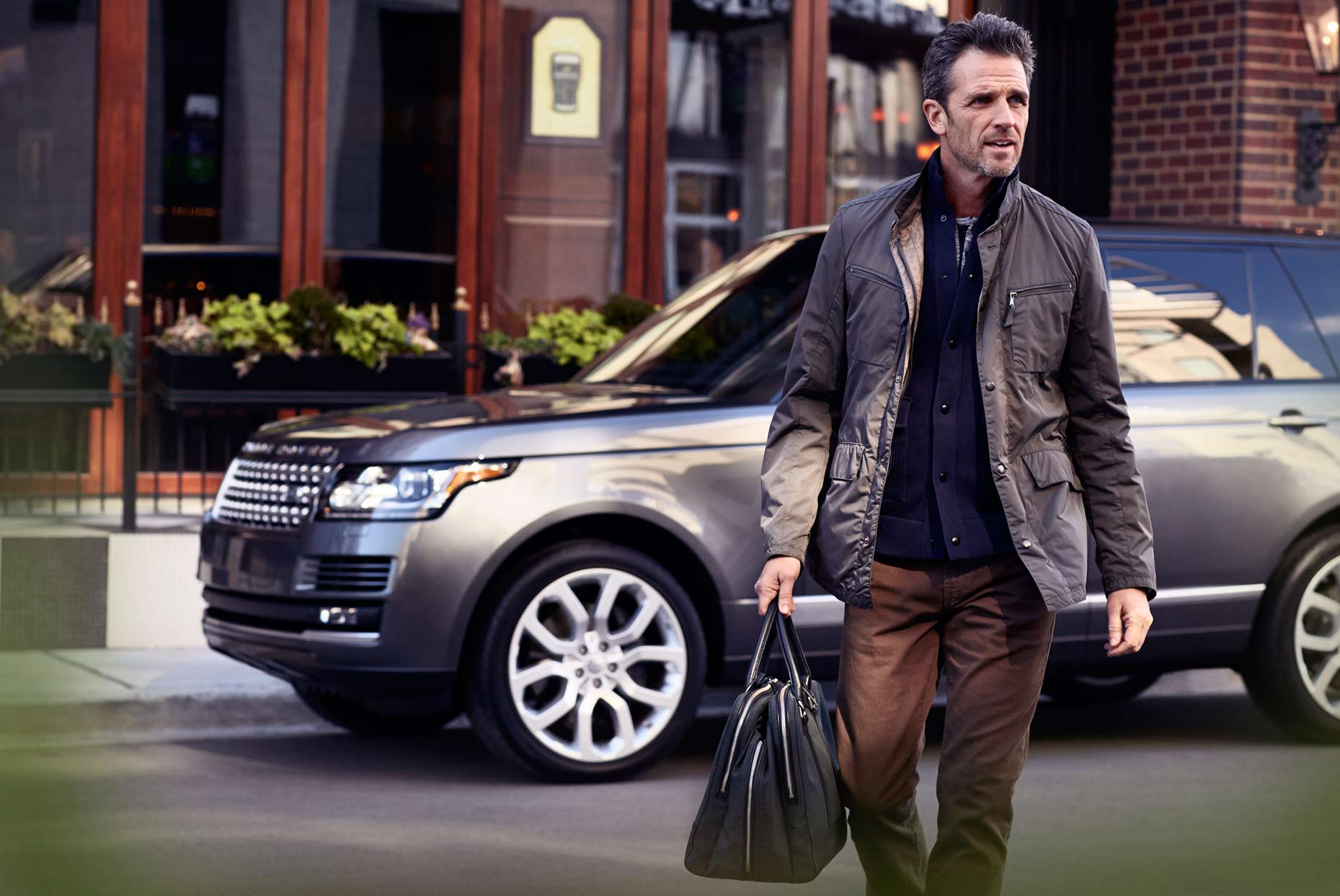 Mark DeLong - Commercial Photography - Well dressed middle aged man walking away from SUV carrying a satchel.