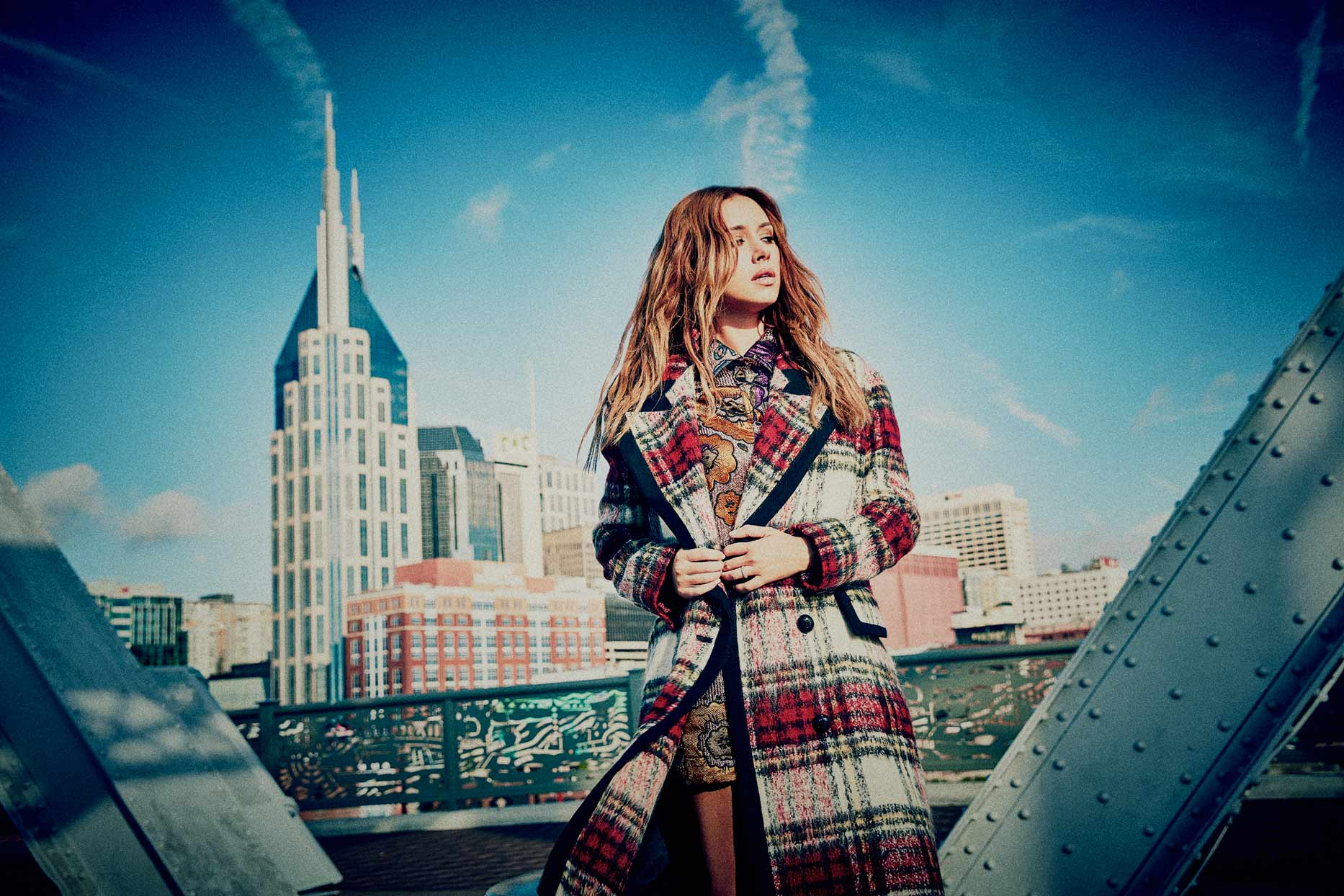 Mark DeLong - Celebrity Photographer - Actress in a plaid coat in front of a city landscape.