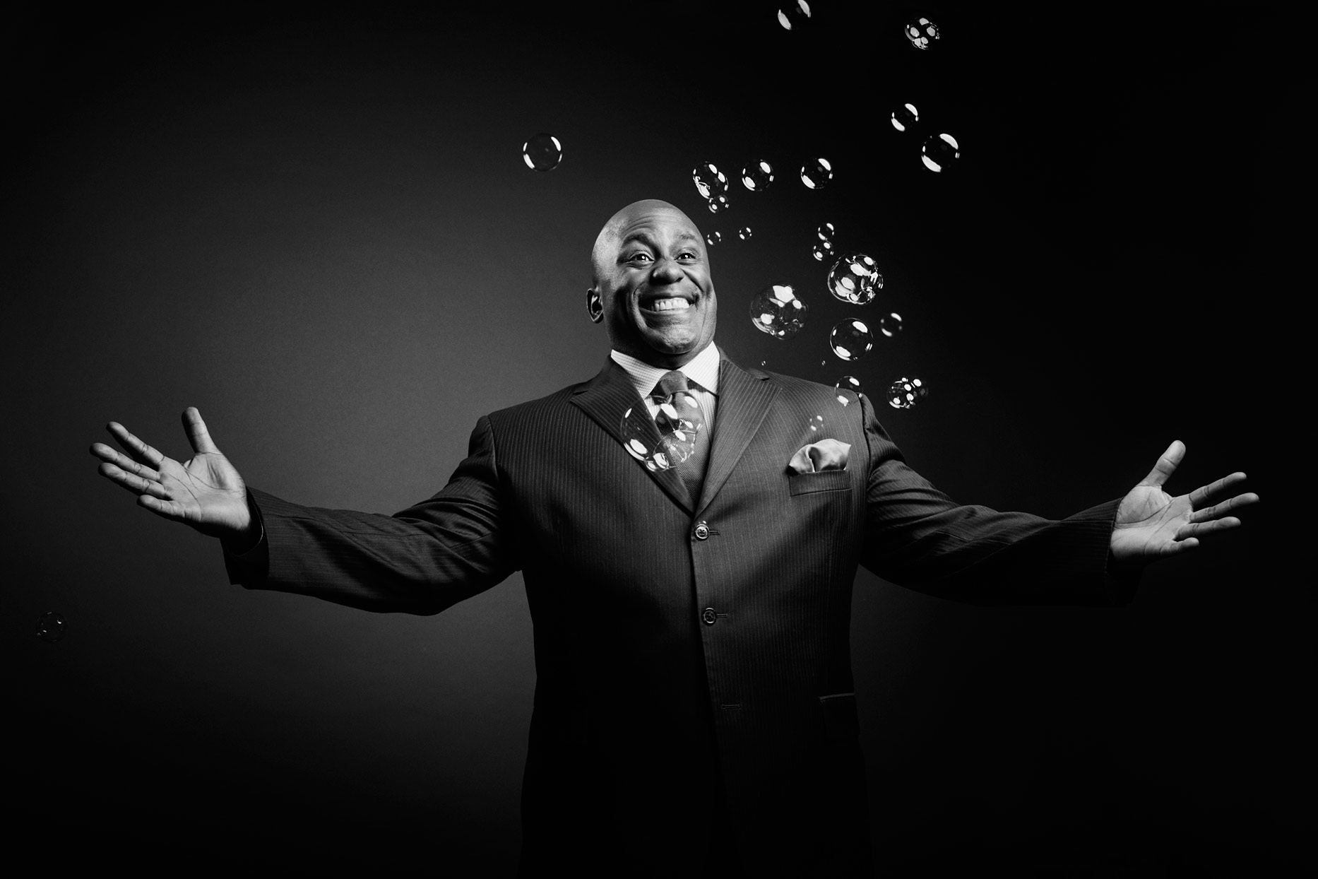 Mark DeLong - Celebrity Photographer - Actor with arms spread wide with bubbles in front of him.
