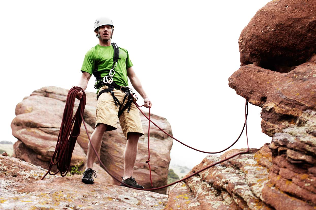 Mark DeLong - Lifestyle Photography - A man in a helmet holding a rope on red rocks