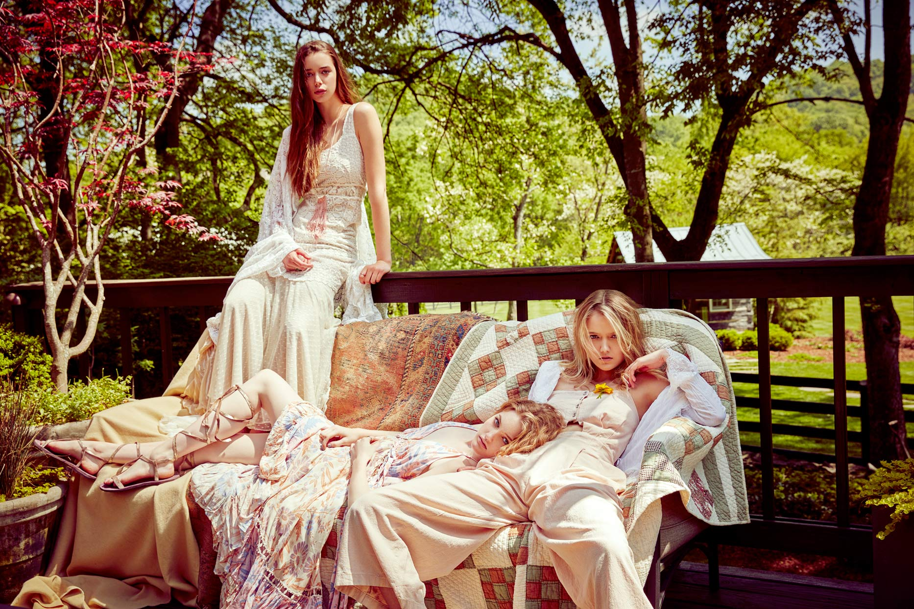 Three women wearing vintage designer dresses and clothing sitting on quilts at a country home - Mark DeLong: Fashion Gallery