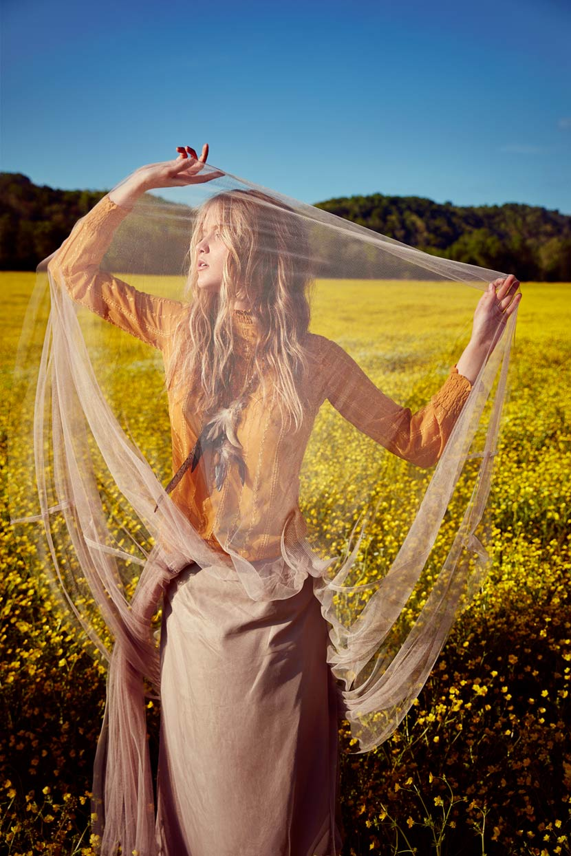 Woman holding up see through tan lace while wearing gold orange long sleeve top in a field of yellow flowers - Mark DeLong: Fashion Gallery