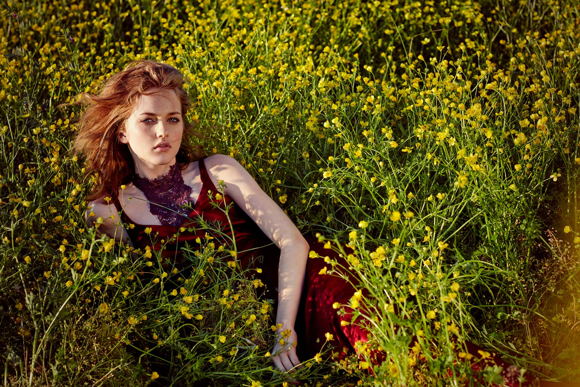 Red haired woman with freckles wearing silk red dress laying in field of yellow flowers - Mark DeLong: Fashion Gallery