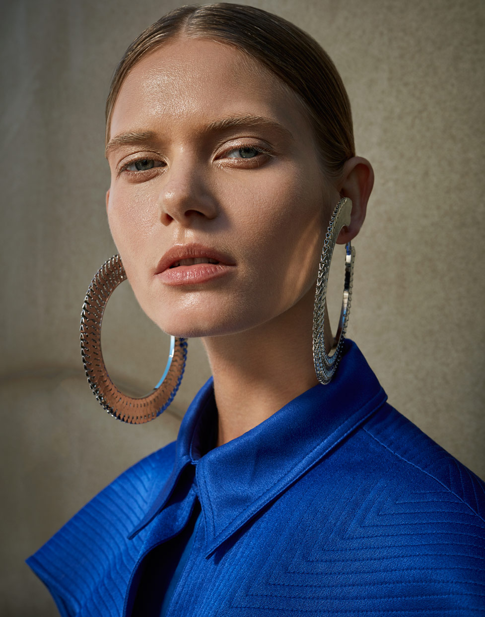 Portrait of woman with hair parted in the middle wearing large silver hoop earrings and blue collar top - Mark DeLong: Fashion Gallery