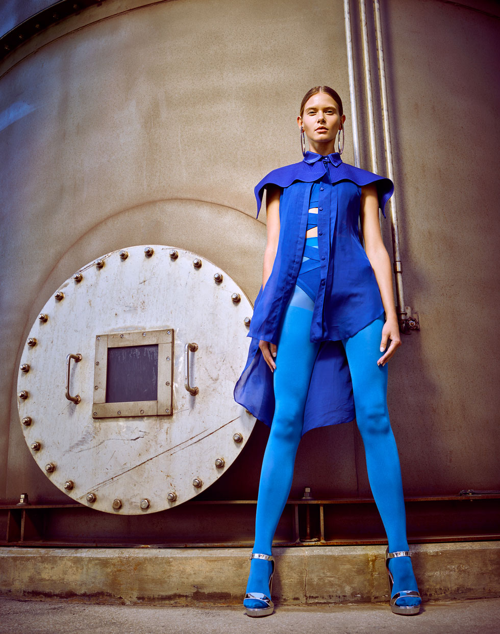 Woman standing in all blue: blue elegant top with blue leggings and blue heels in front of an industrial storage tank - Mark DeLong: Fashion Gallery
