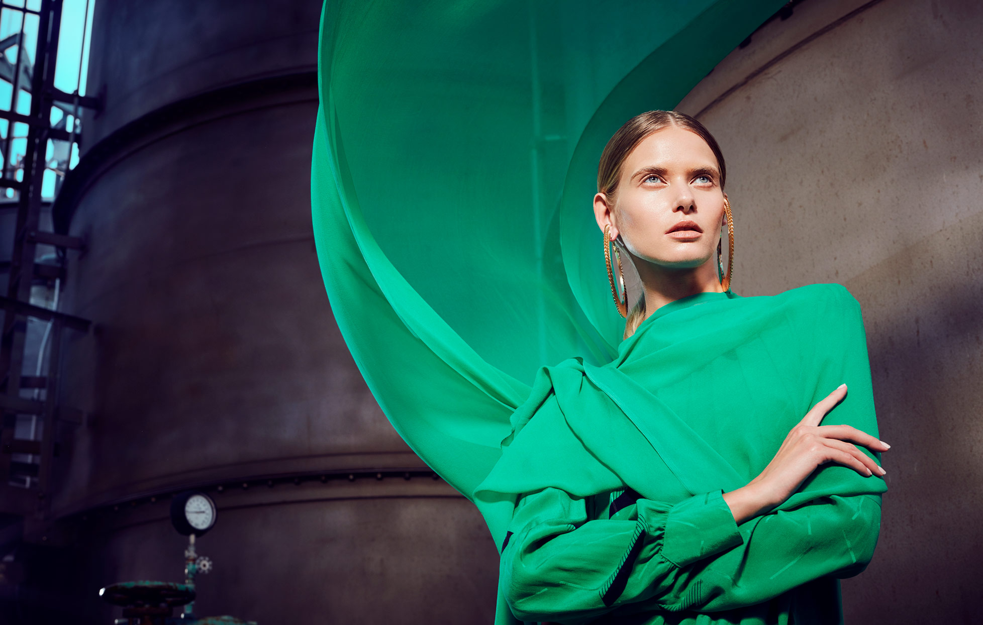 Woman posing with arms crossed wearing green top and flowing green cape behind - Mark DeLong: Fashion Gallery