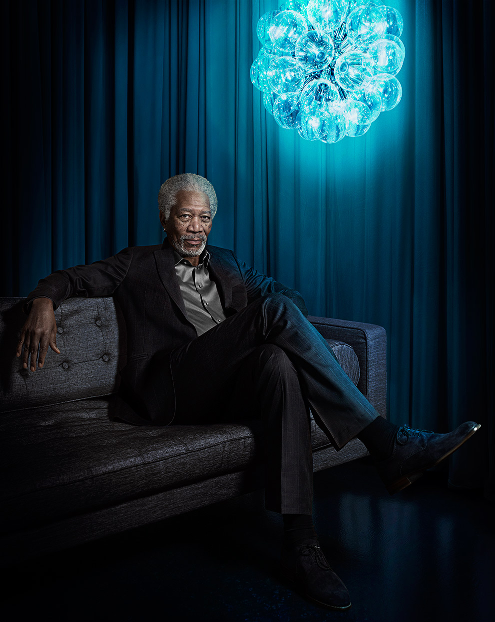 Mark DeLong - Celebrity Photographer - Morgan Freeman sitting on a brown couch in a blue room.